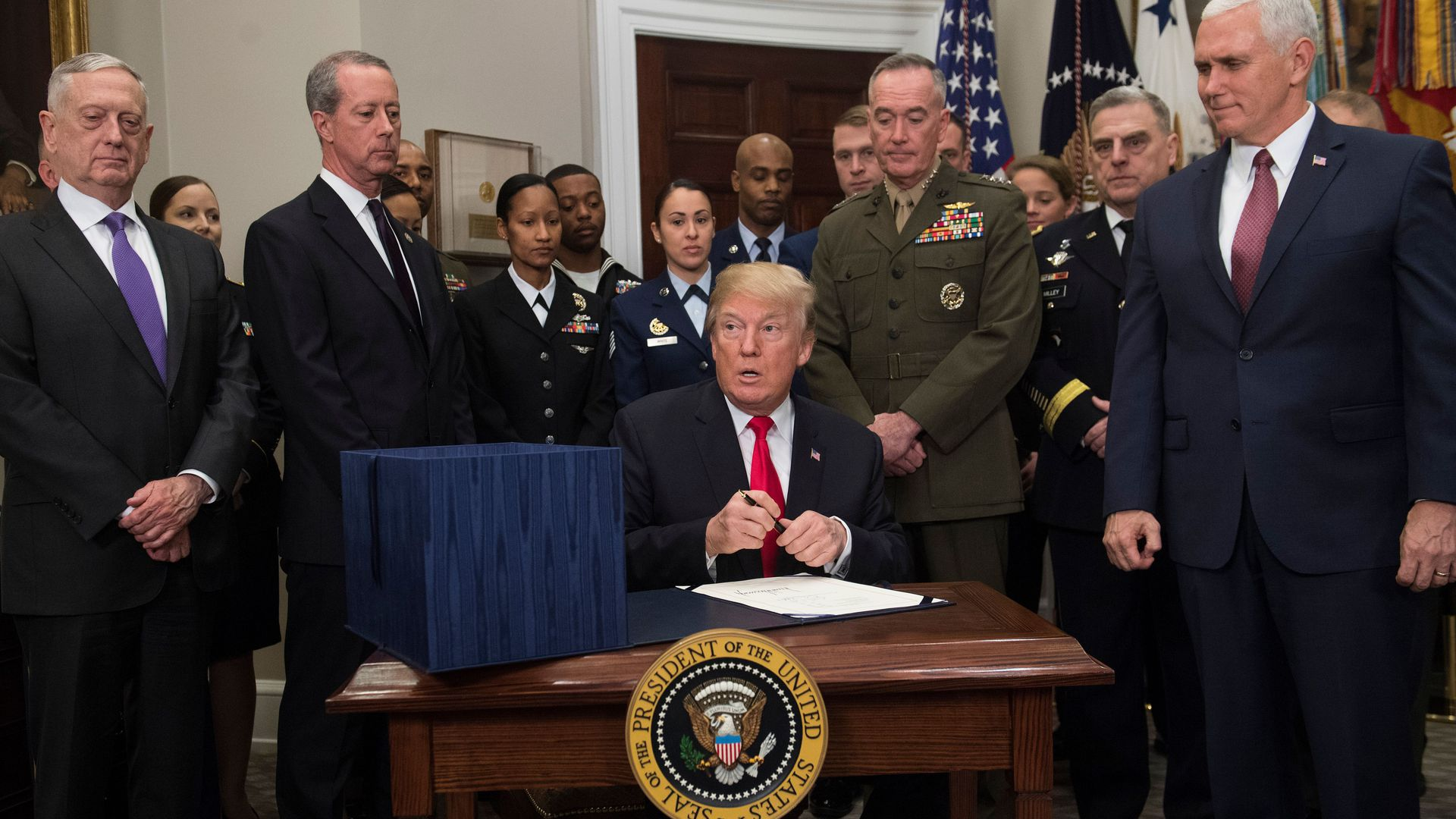 President Donald Trump, surrounded by military officials and members of Congress.