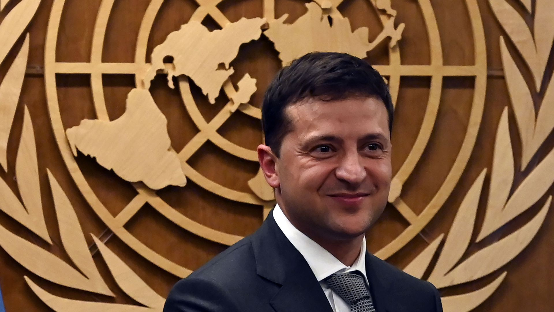 Zelensky in front of a wall-mounted UN logo