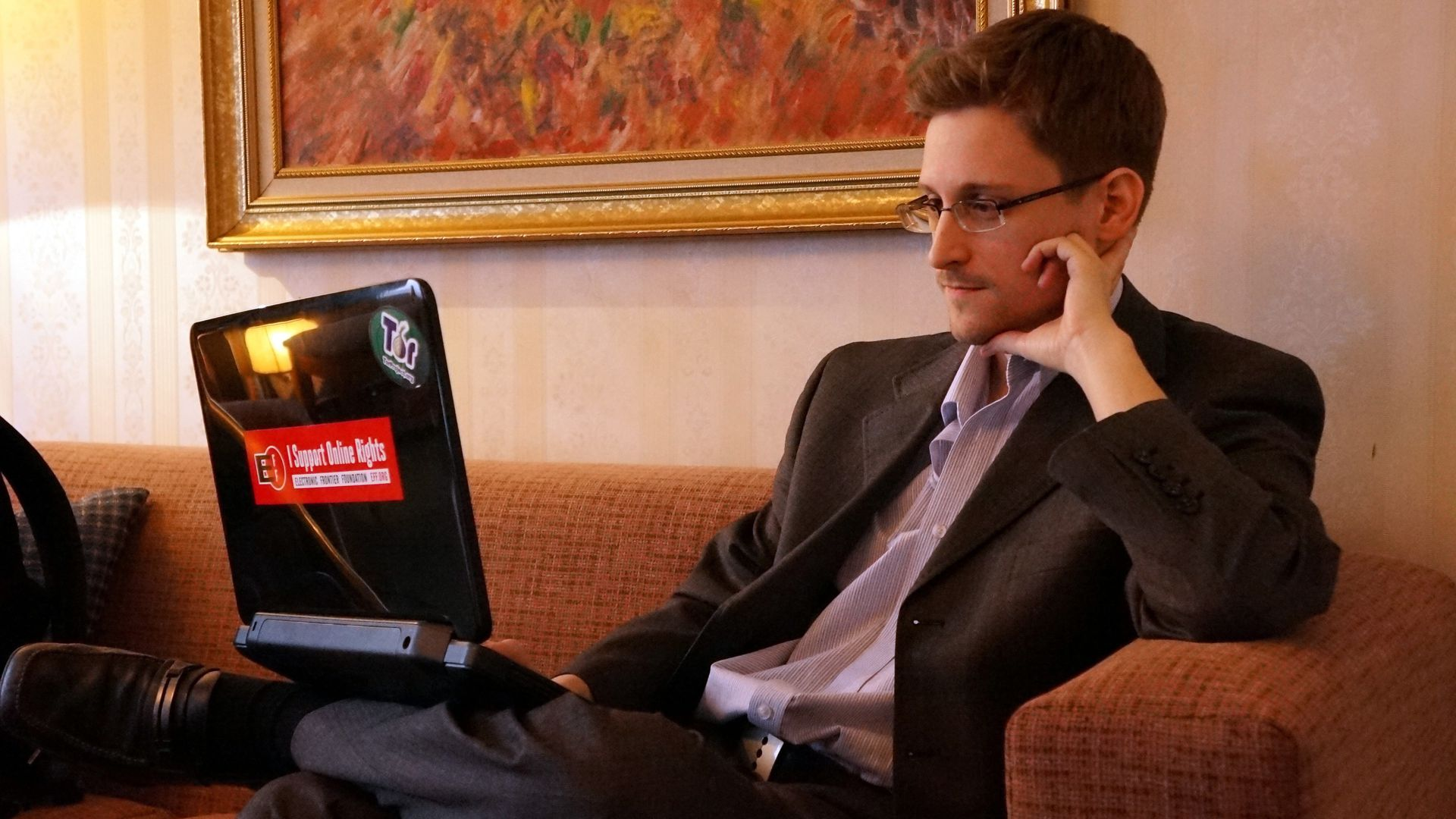 Snowden looking at a laptop.