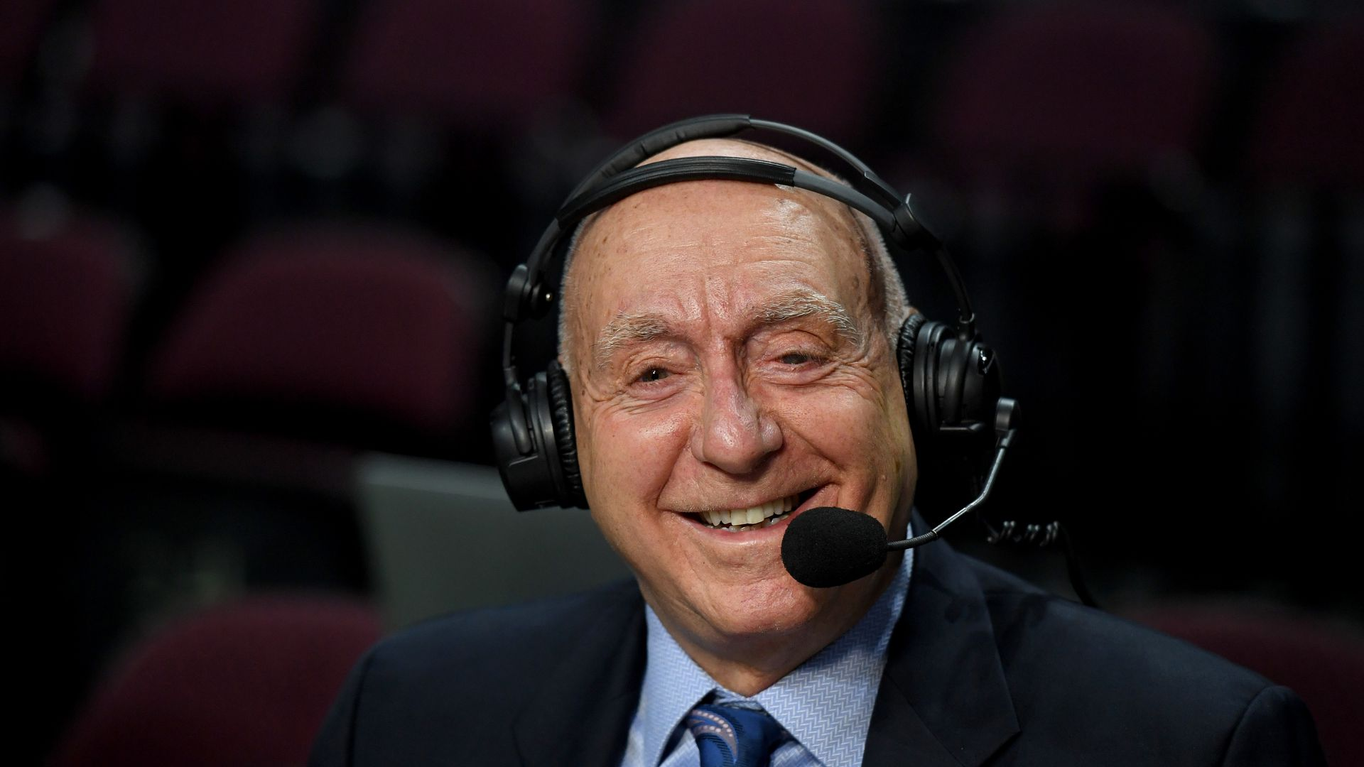 Dick Vitale sits with a microphone in front of his face smiling.