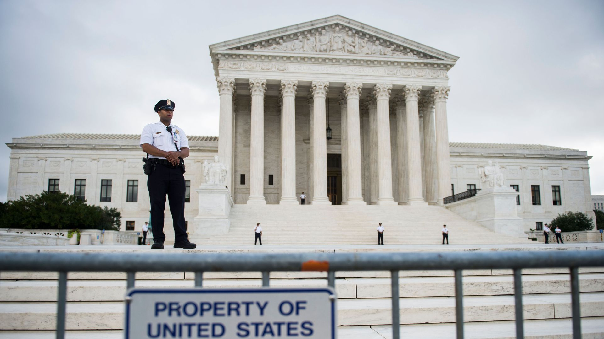 A security officer stands guard on the steps of the Supreme Court