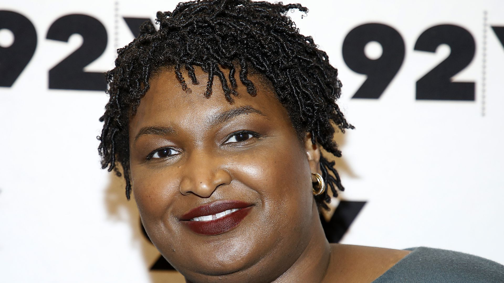 In this image, Stacey Abrams smiles at a camera.
