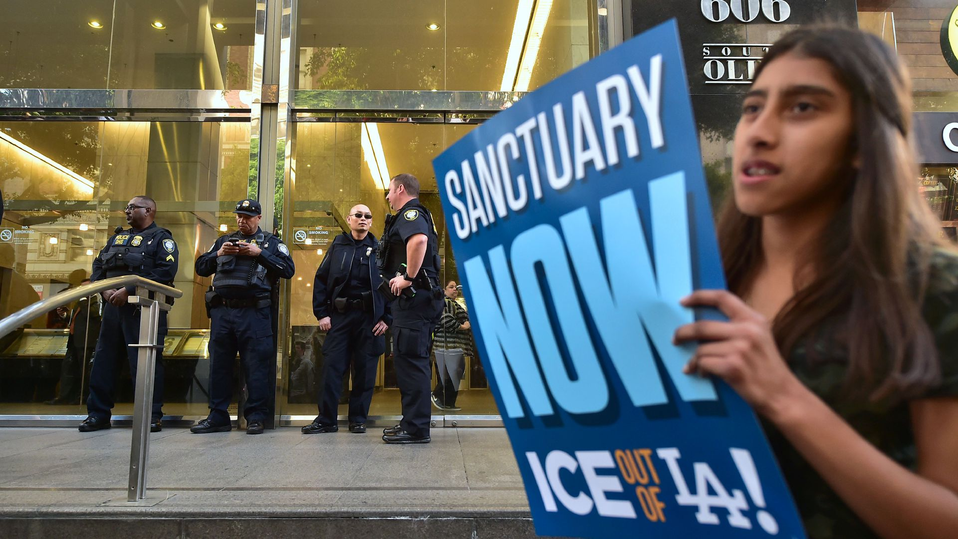Department of Homeland Security police officers stand guard in front of a Los Angeles Immigration Court building during a rally against an arrest by ICE agents.