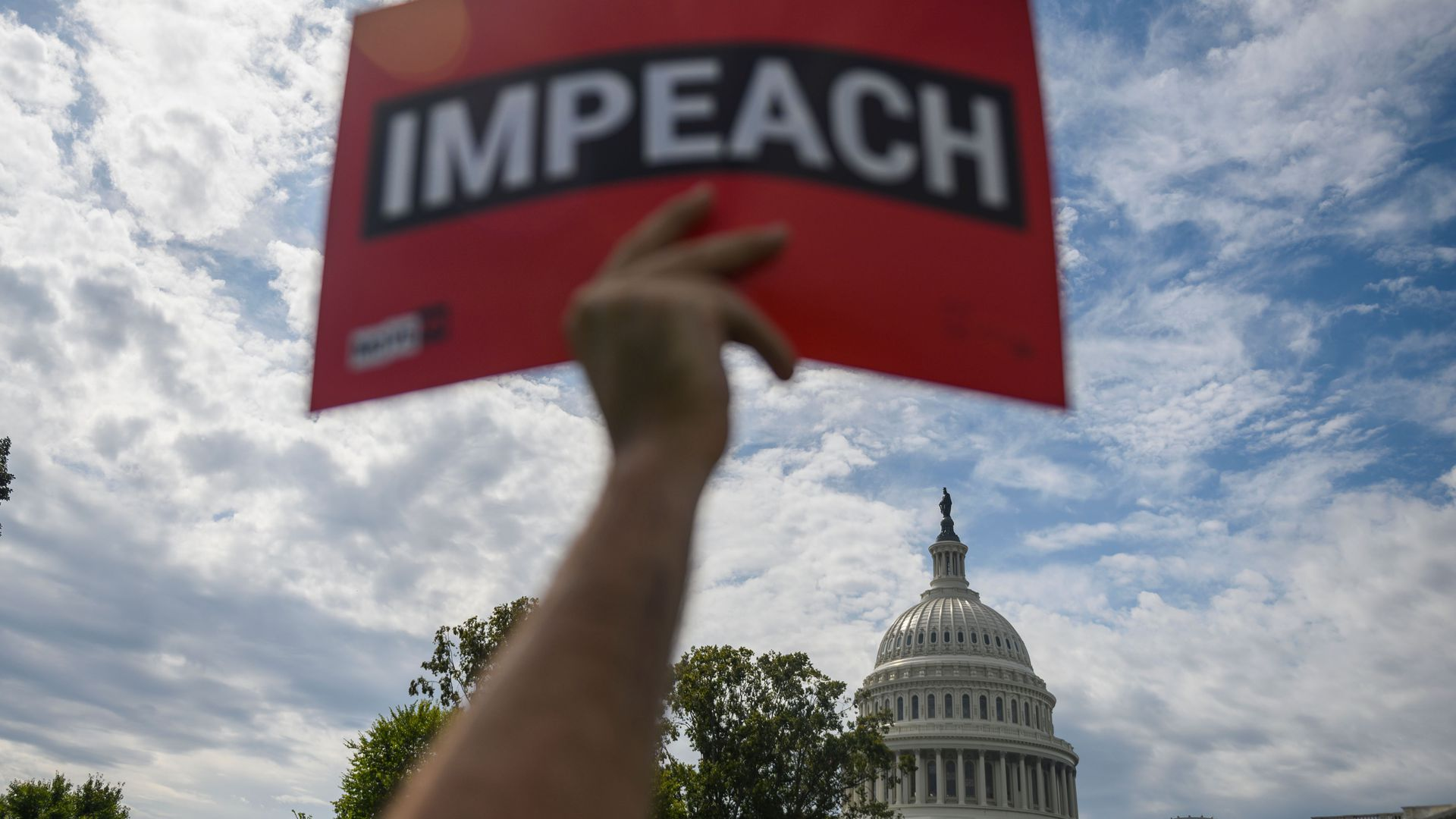"A protester holds up a sign reading ""impeach"" outside the US Capitol building"