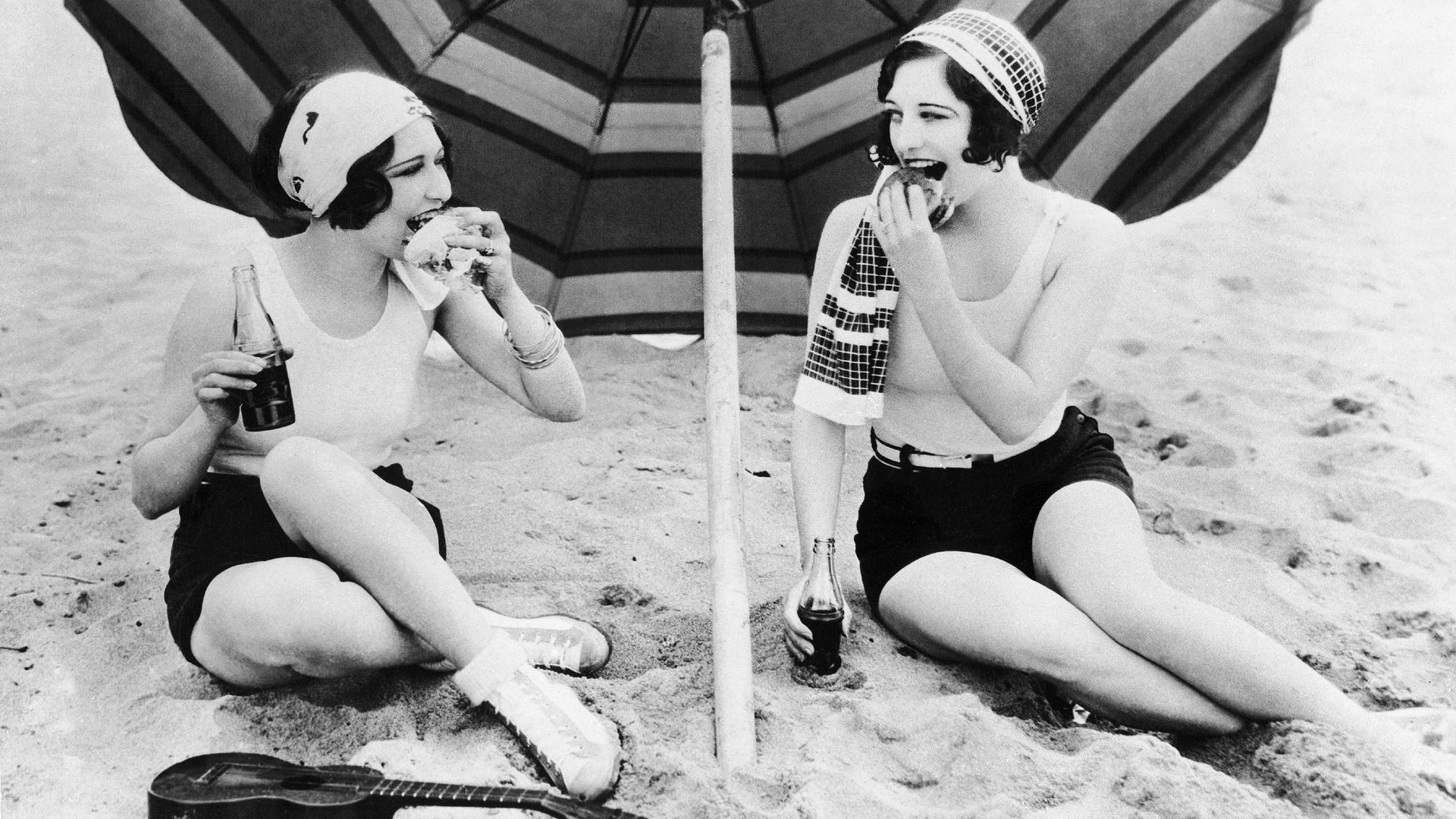 Actresses Dorothy Sebastian and Joan Crawford eating burgers