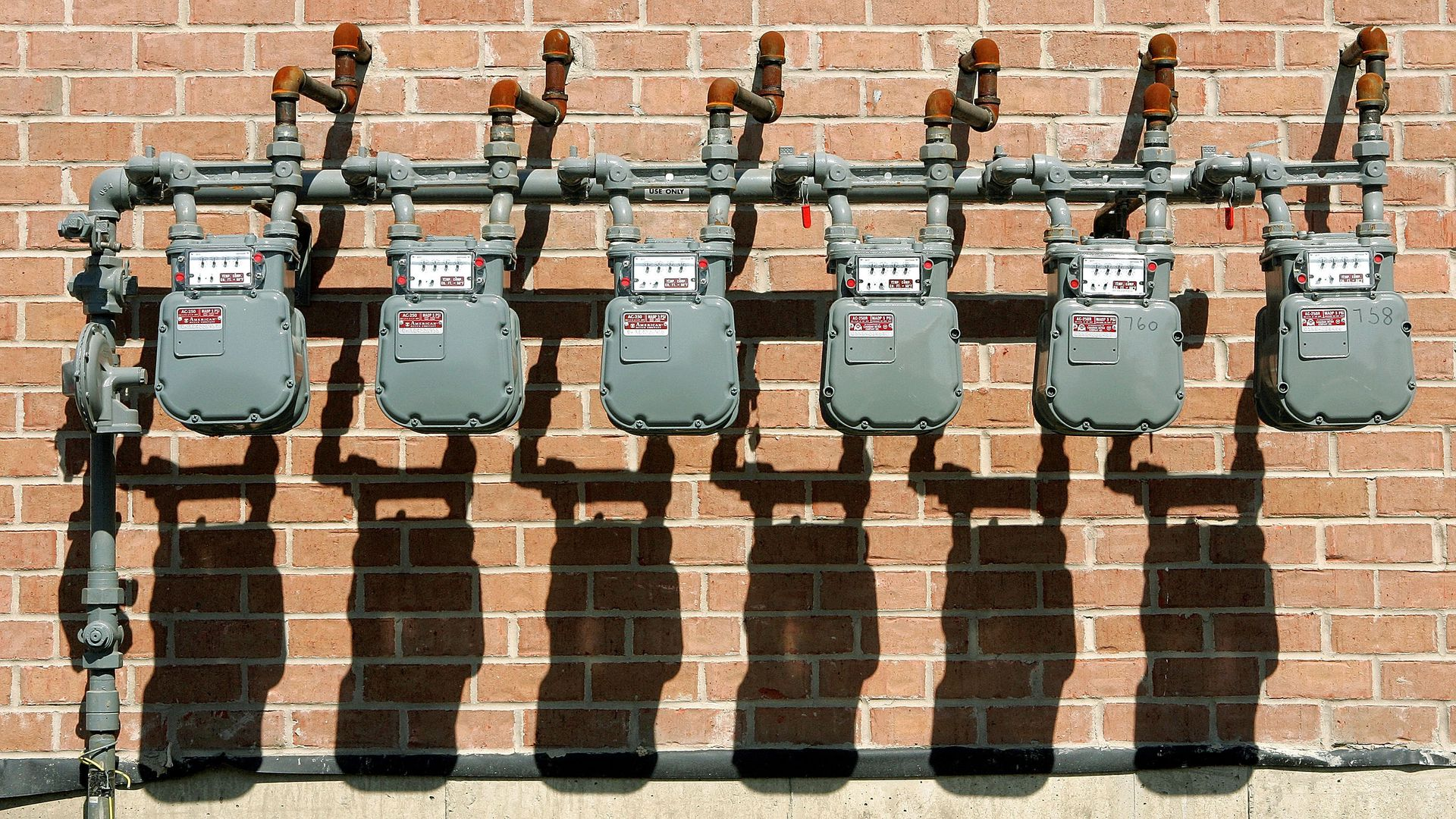 natural gas meters against a brick wall