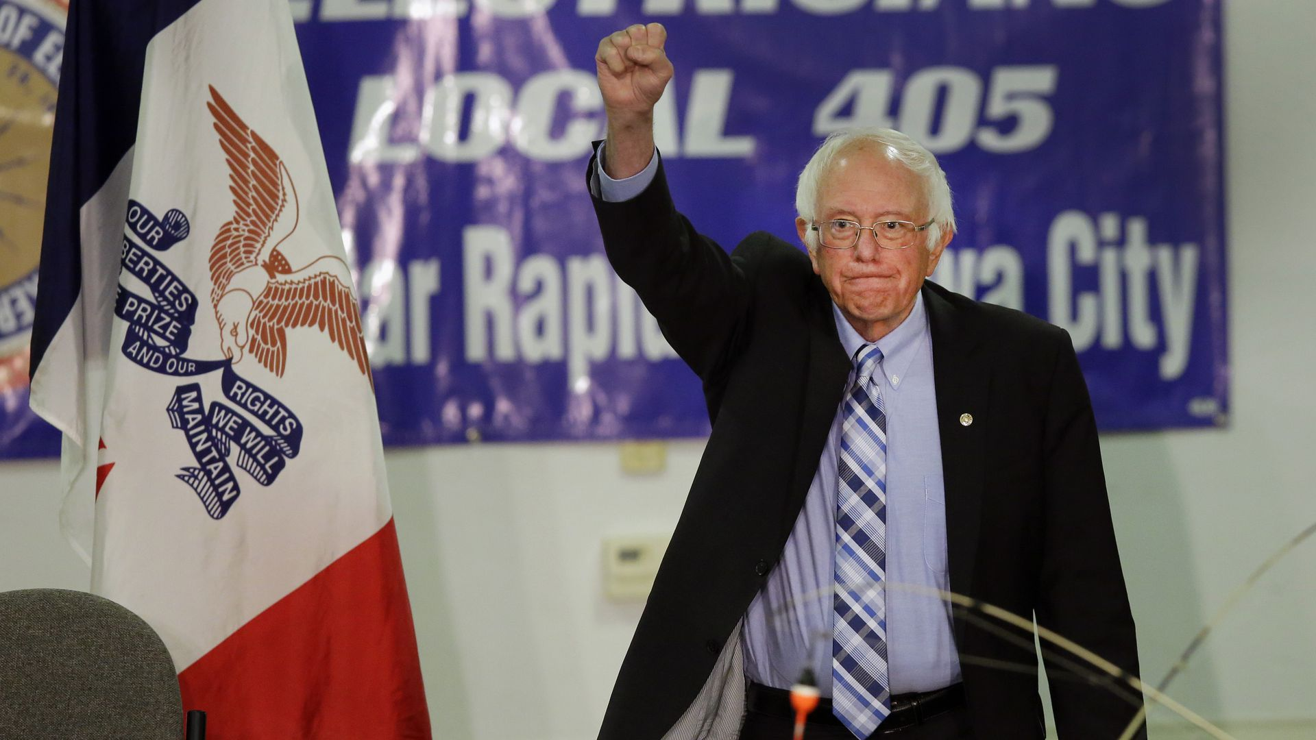 Bernie Sanders raises a fist at a crowd.