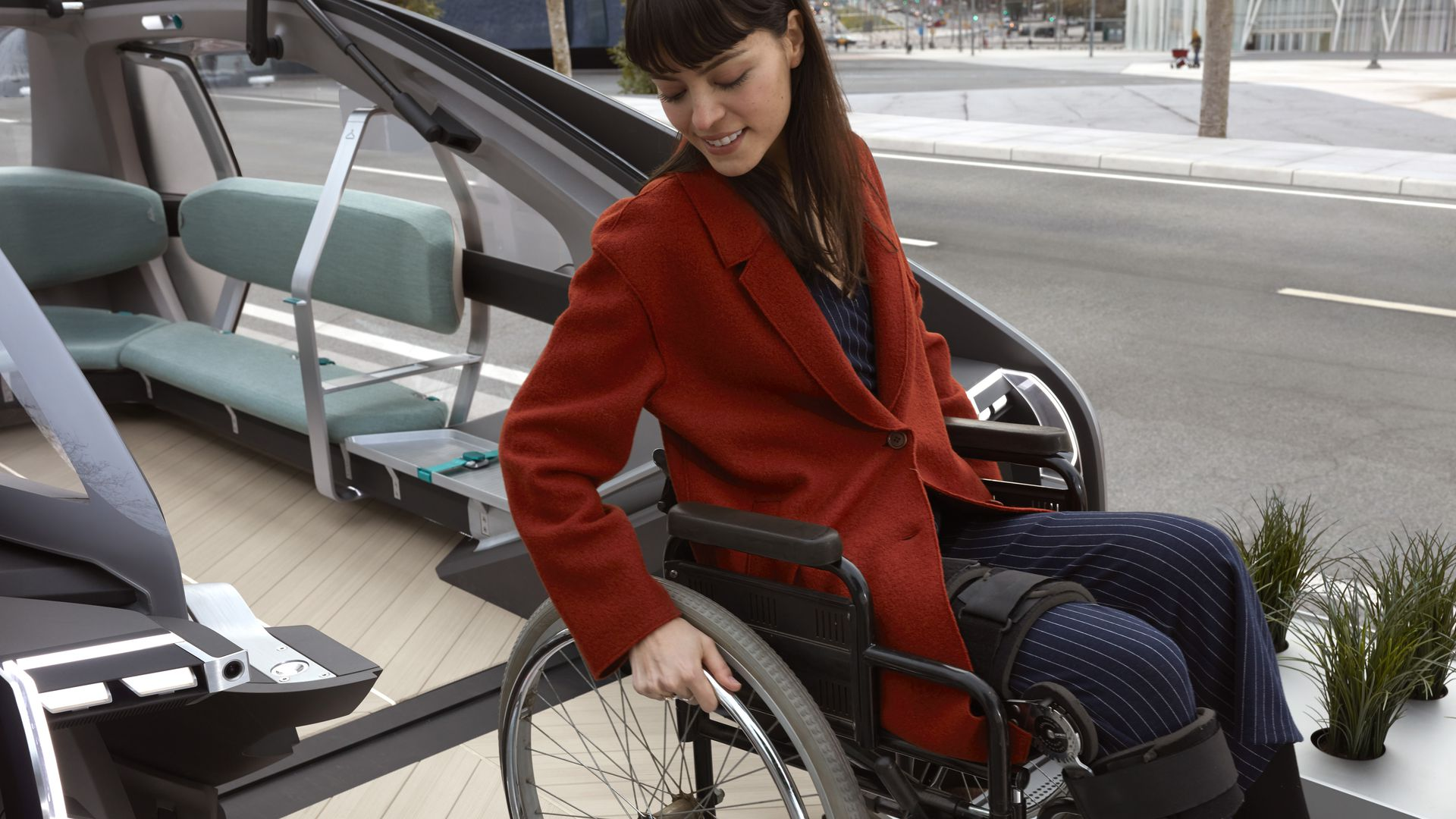 A woman in a wheelchair uses a ramp on a Renault EZ-GO concept car