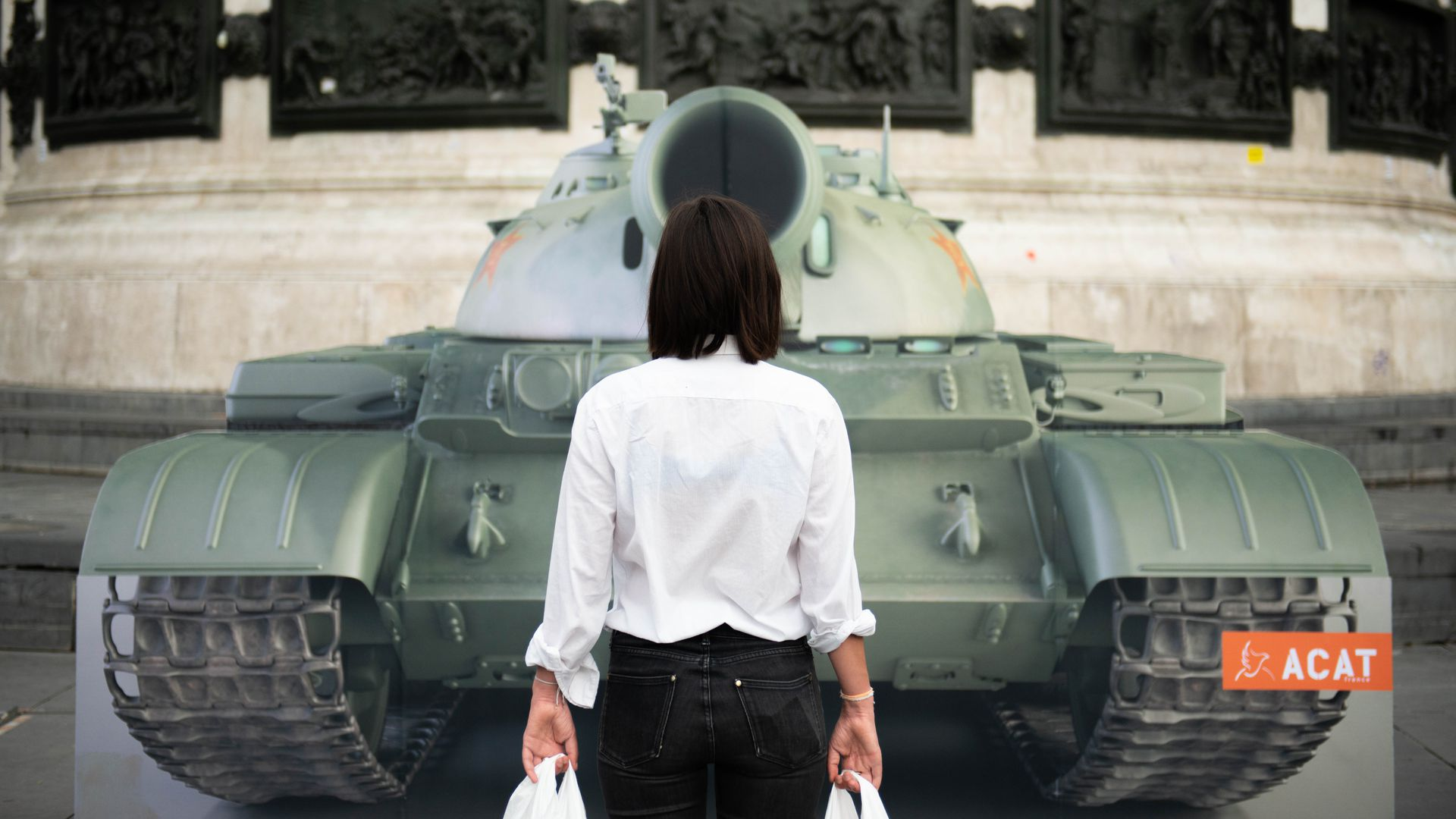 in front of a fake tank on the Place de la Republique square in Paris to mark the 30th anniversary of Tiananmen Square crackdown in China