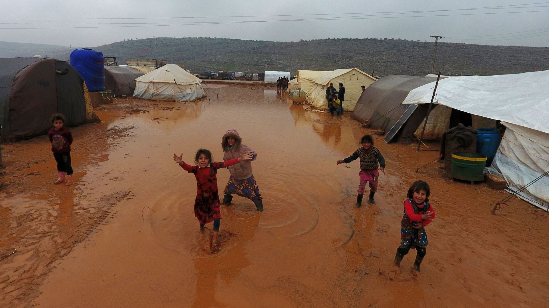 children playing in between tents on wet ground of refugee camp