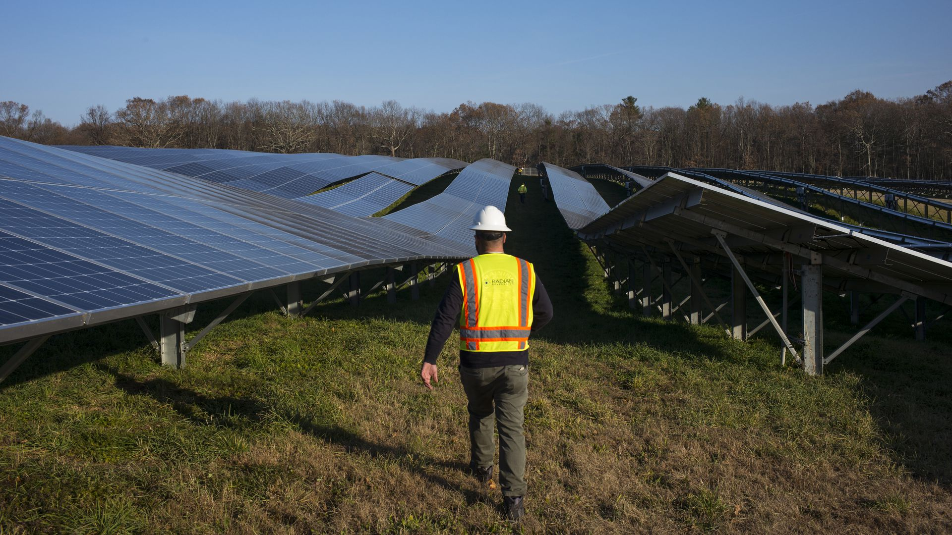 A man walks through a field with solar panels