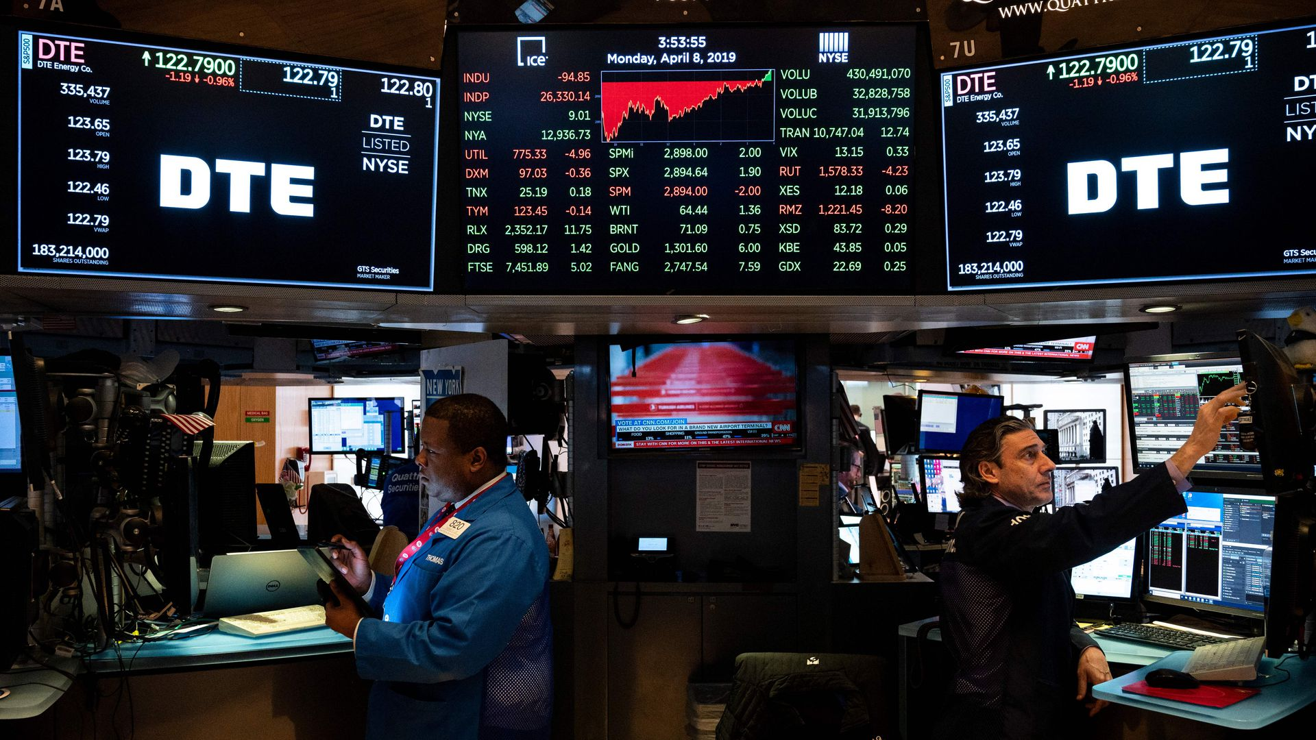 In this image, two men stand facing away from each other on the stock market trading floor, with three screens above and behind them.