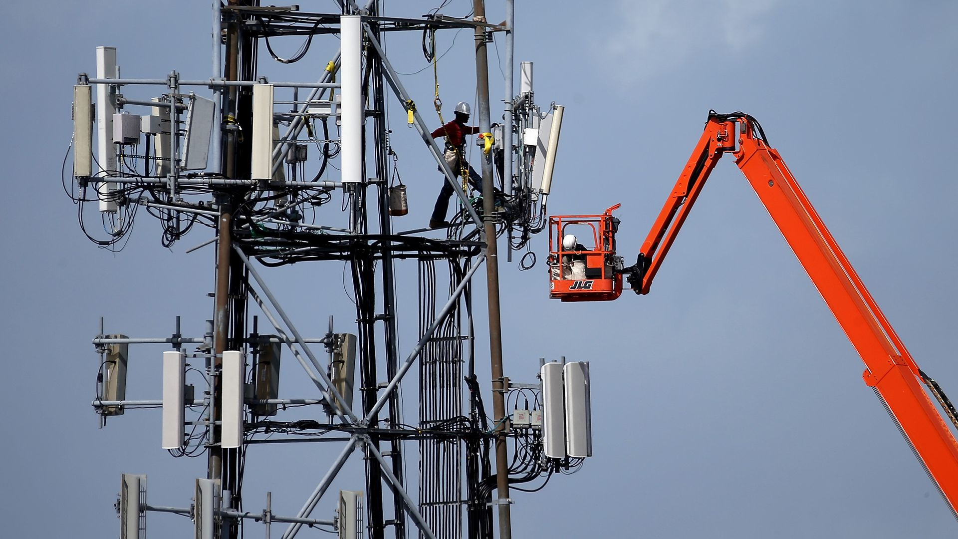 A worker climbs a cellular communications tower