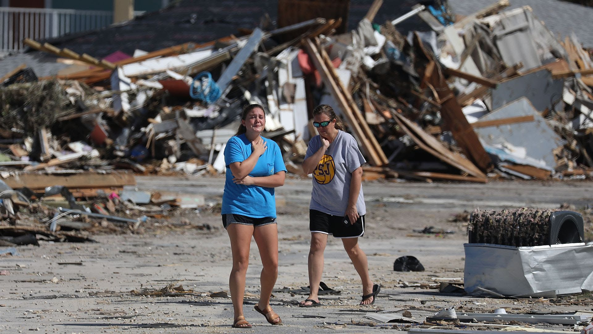Two people stand among wreckage from Hurricane Michael.