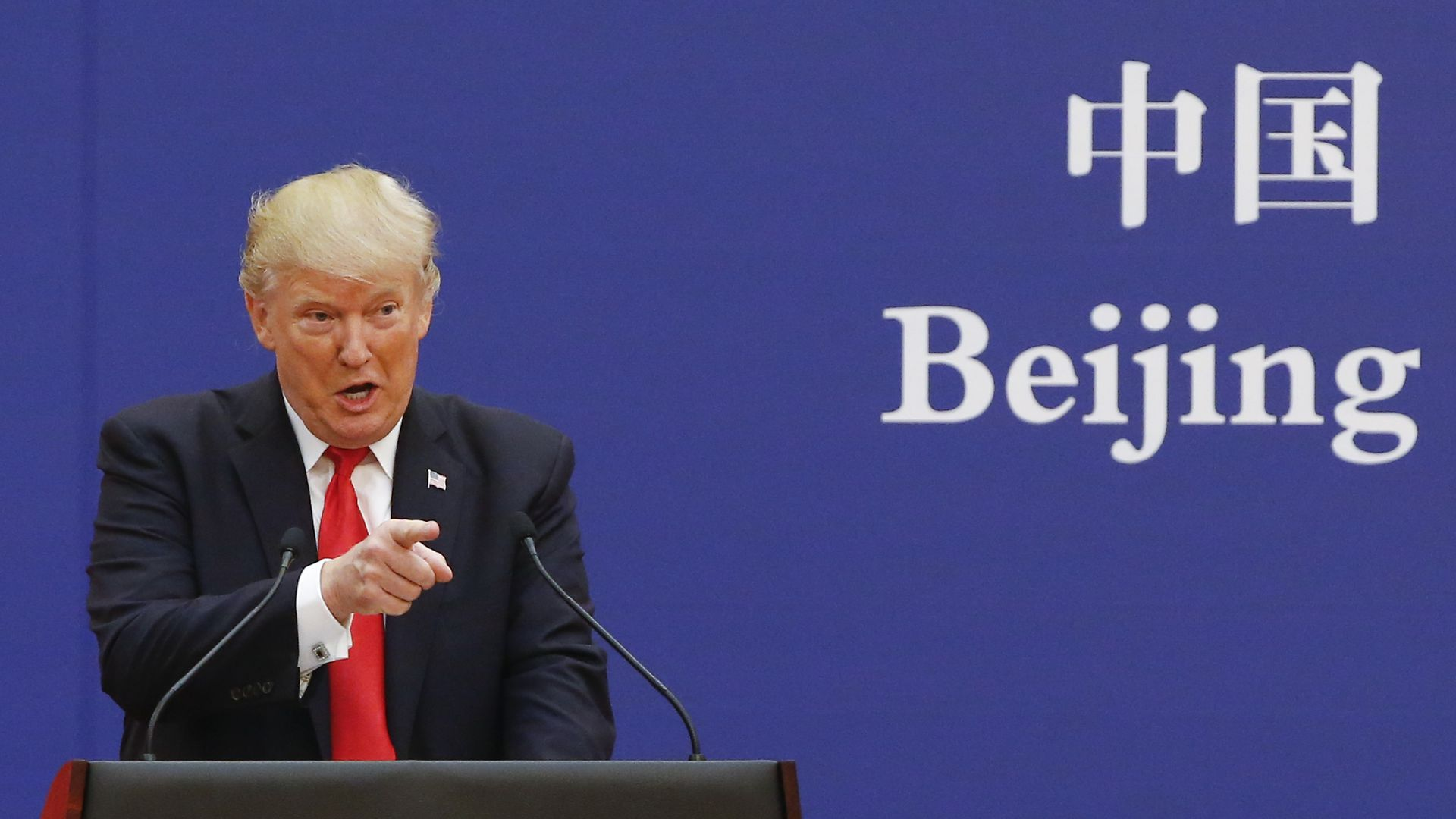 "Trump speaks at a podium in Chine in front of a screen that says ""Beijing"""