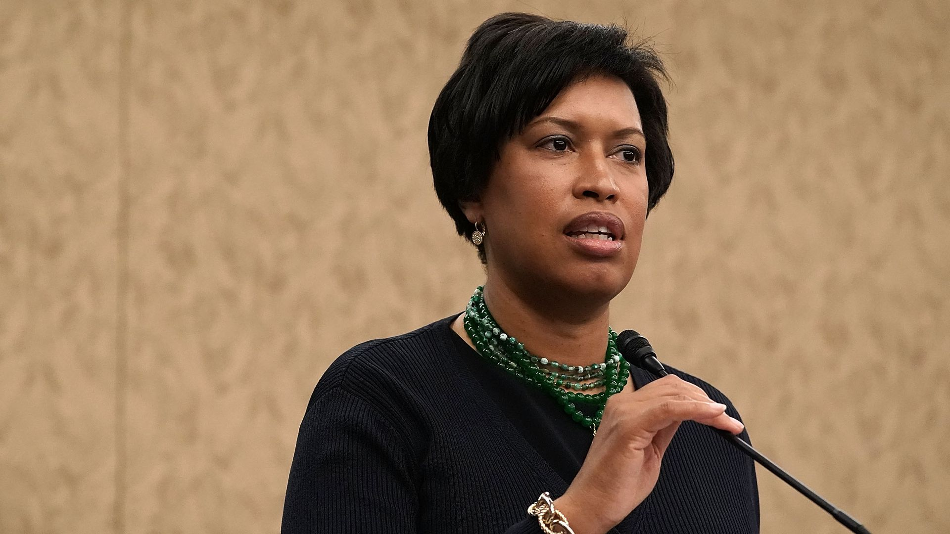 Mayor Muriel Bowser speaks into a microphone at a podium