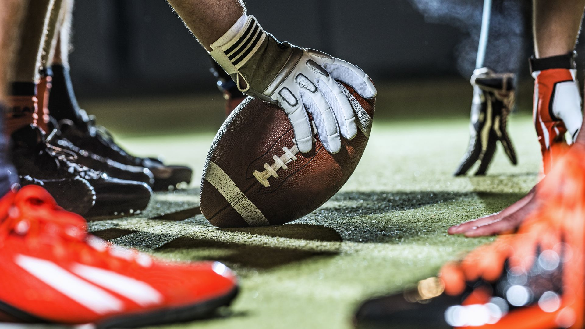 A football player with a football on a field getting ready to play