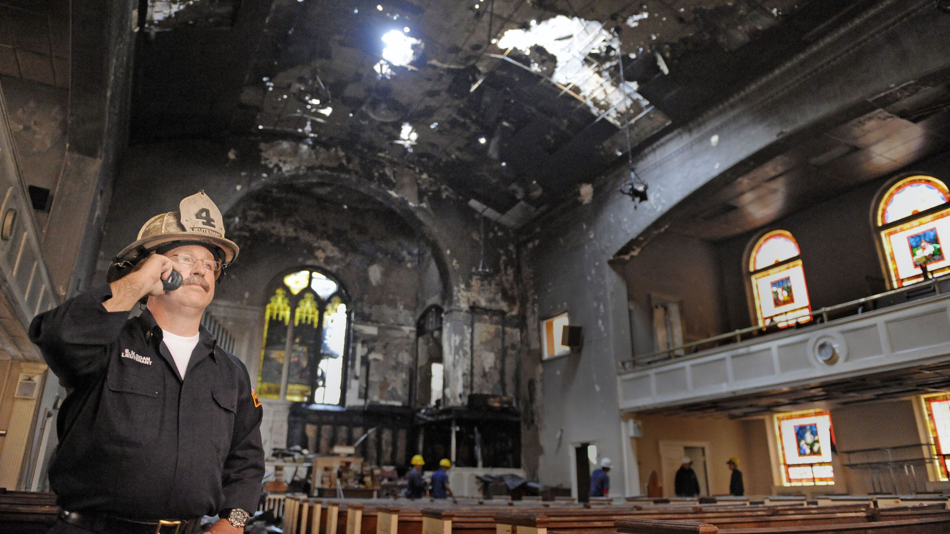 Fire Lt. Sean Egan makes a cell phone call in the burned out interior of Meridian Hill Baptist church.