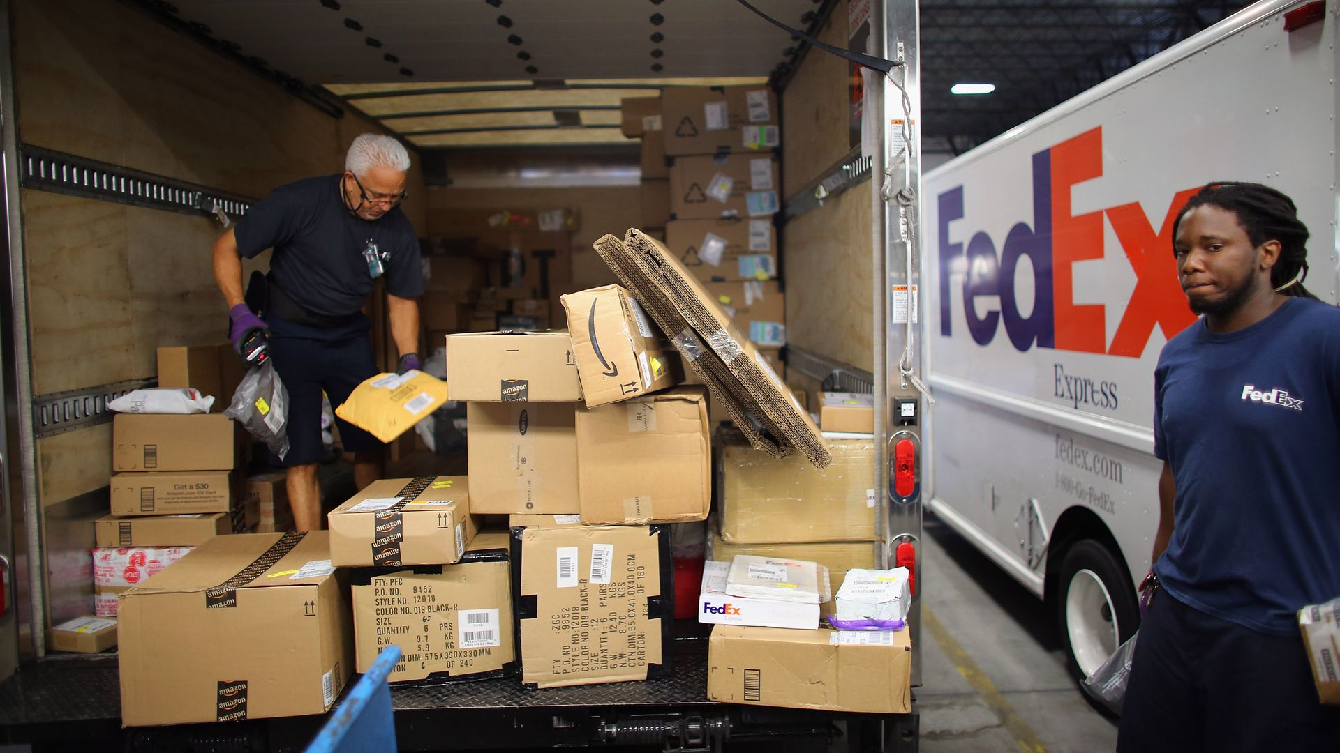 Two men load packages onto a large truck