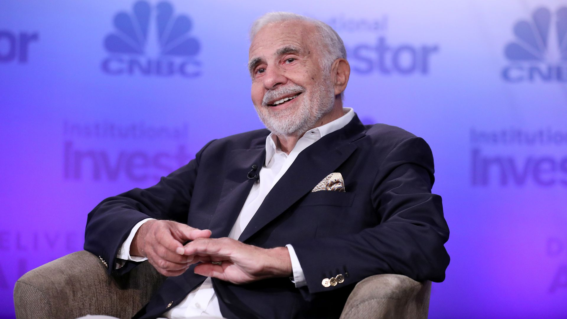 Carl Icahn sitting in a chair smiling on stage at an event