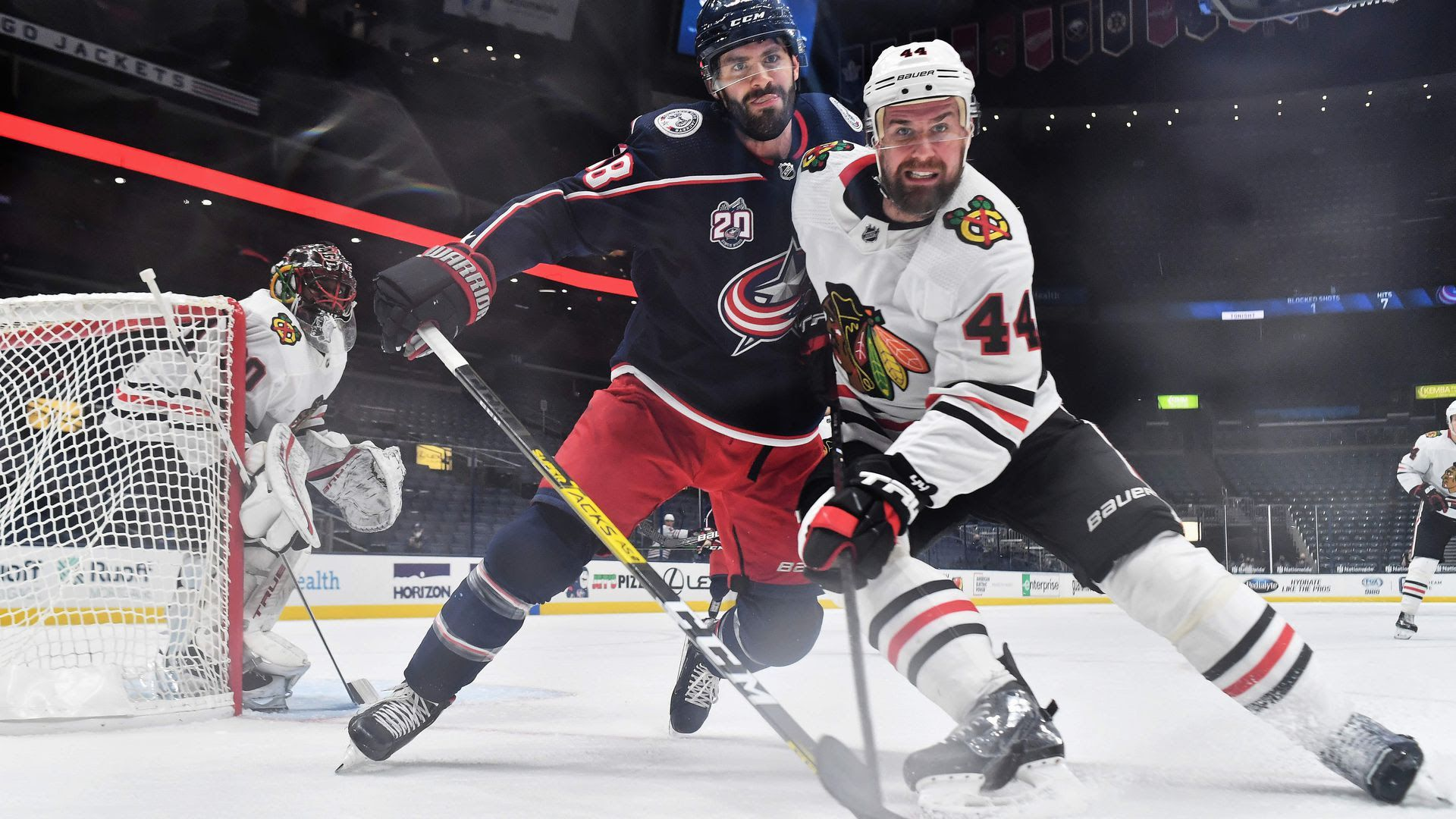 Boone Jenner and a Chicago Blackhawks player battle for position while chasing the puck during a Feb. 25, 2021 game at Nationwide Arena.