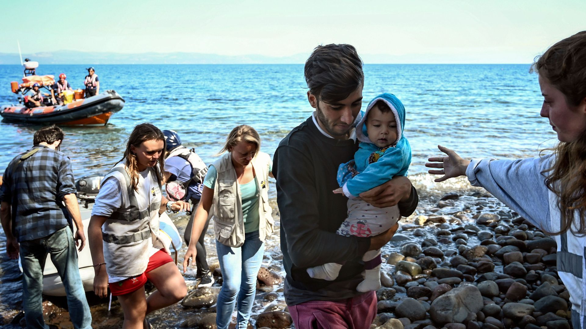 Migrants with a child, helped by rescuers arrive on the Greek island of Lesbos after crossing the Aegean Sea from Turkey