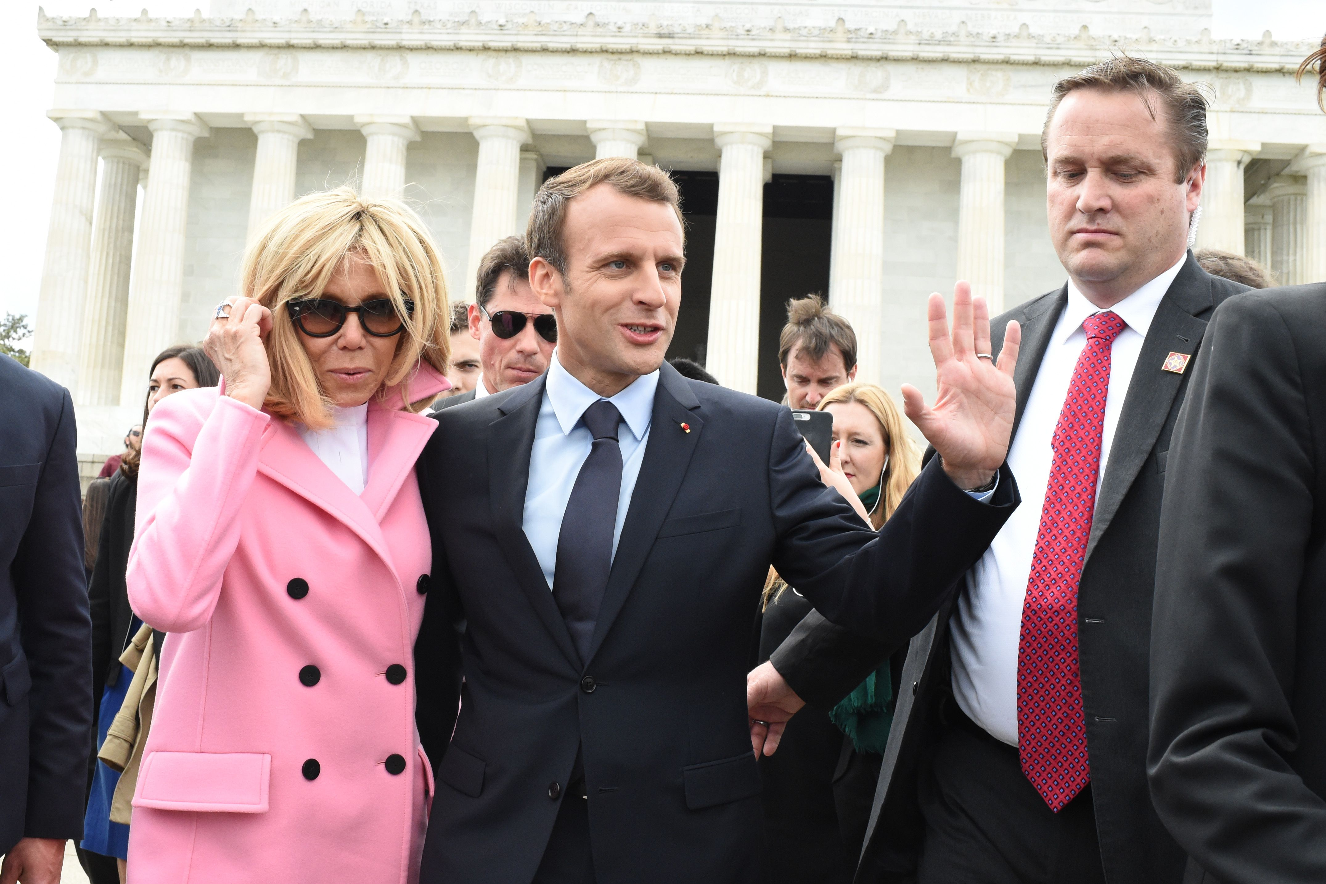 French President Emmanuel Macron and his wife Brigitte Macron smile and wave in front of the Lincoln Memorial.