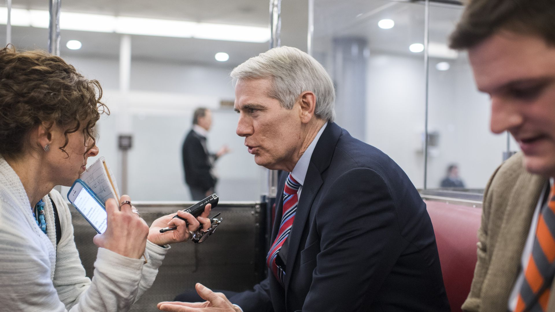 Senator Rob Portman talks to reporters on a train