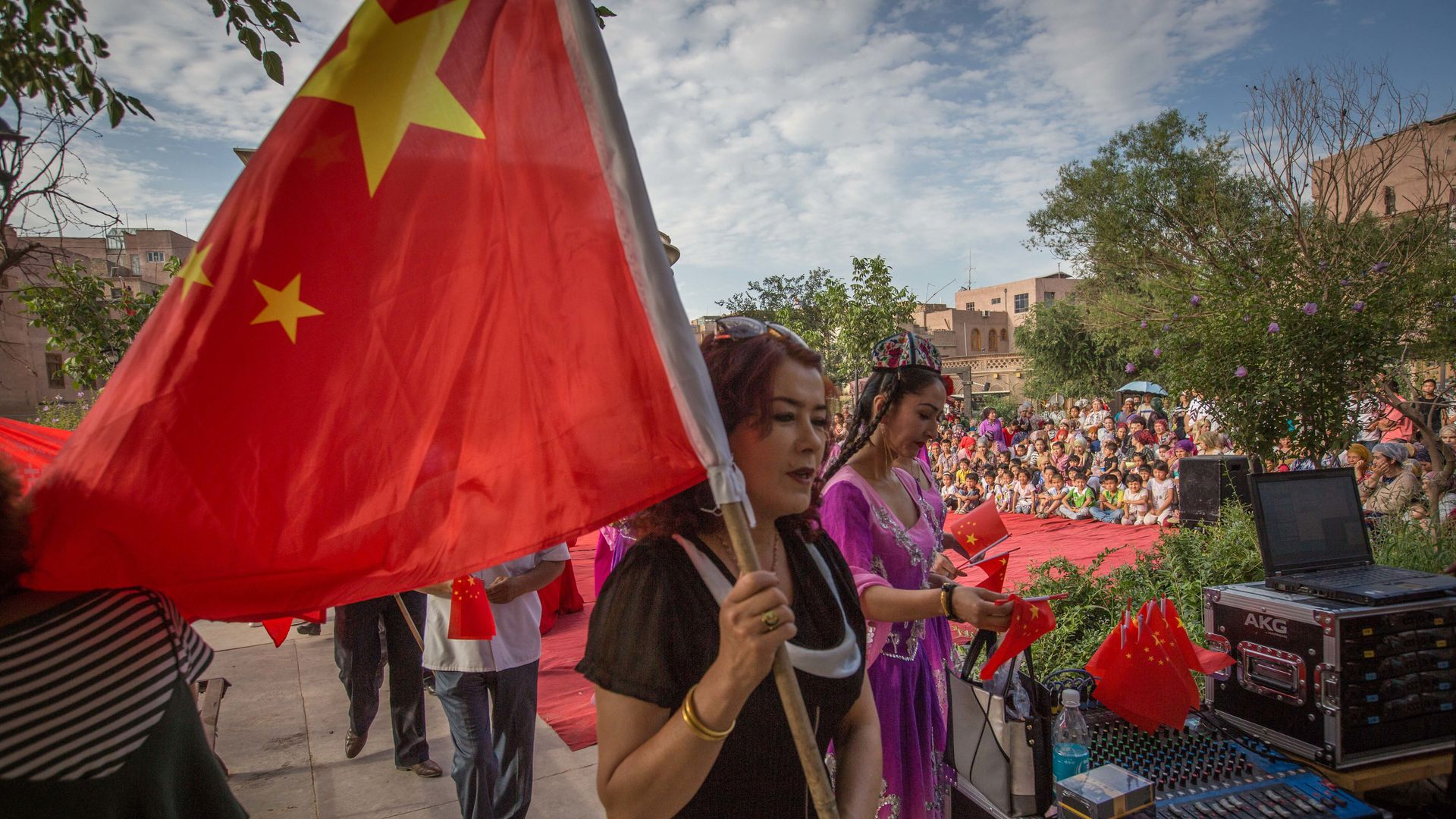 In this image, a Uyghur woman in a black shirt holds a Chinese flag above her as she walks down the street on a cloudy day.