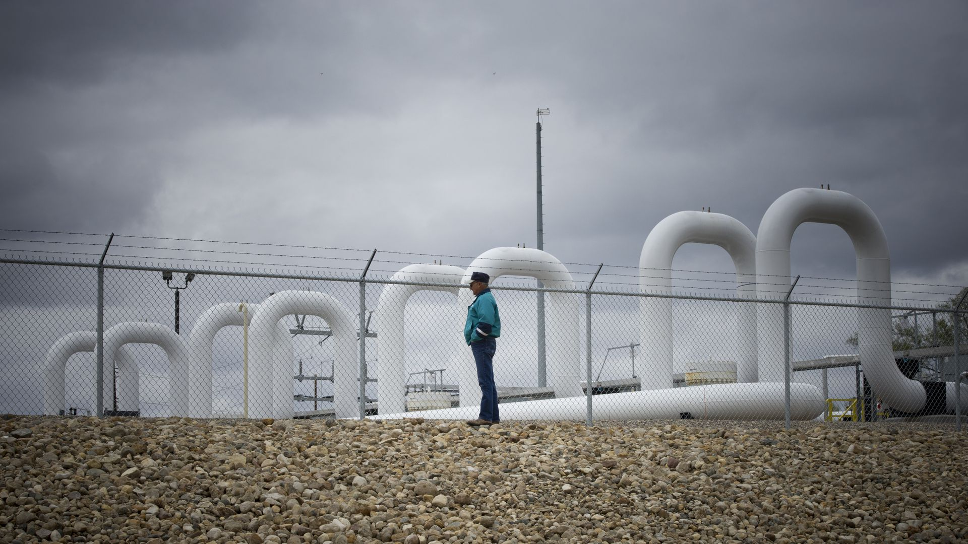 man stands in front of white pipes at oil pumping station