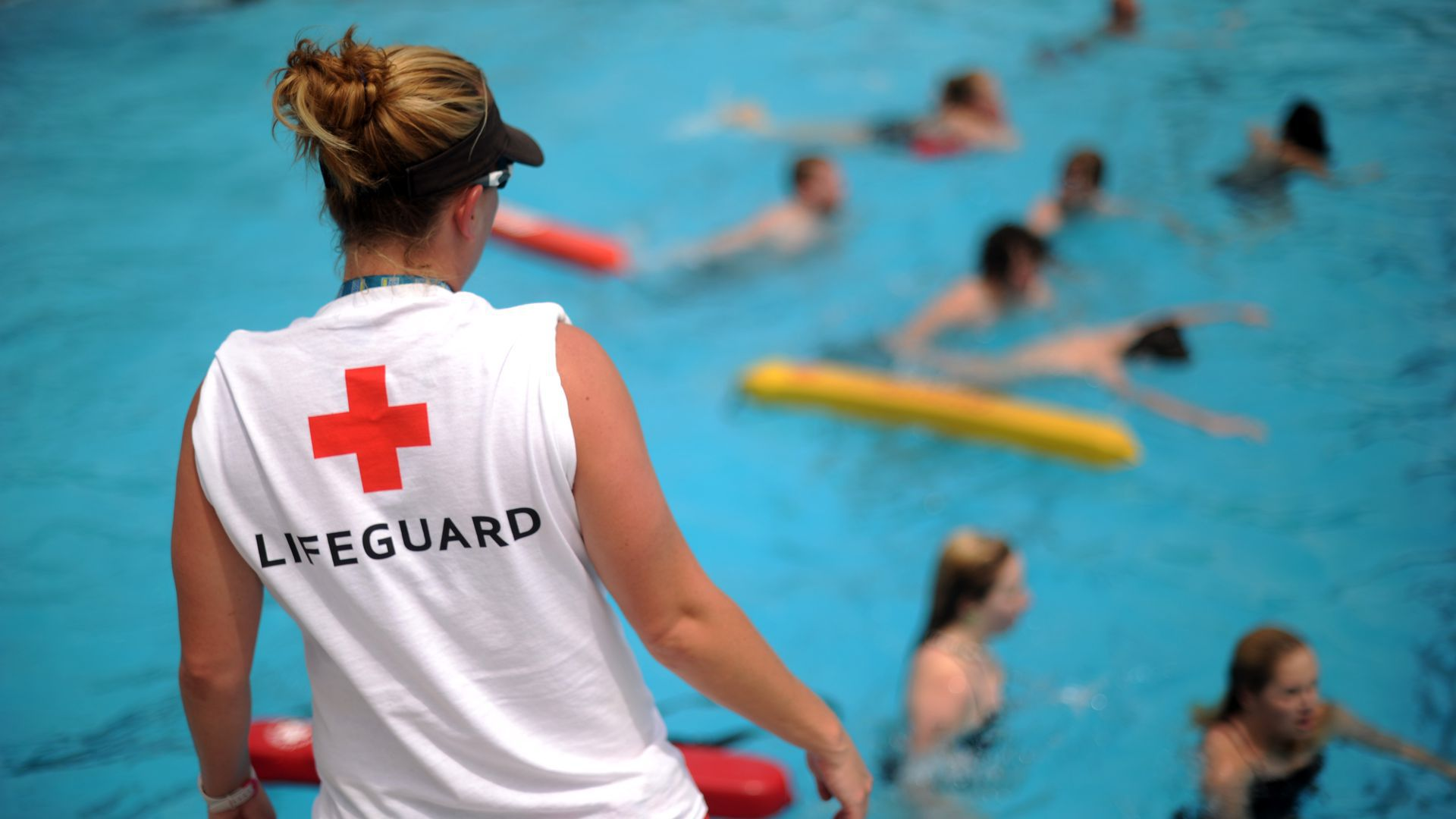 A woman in a lifeguard t-shirt watches a pool