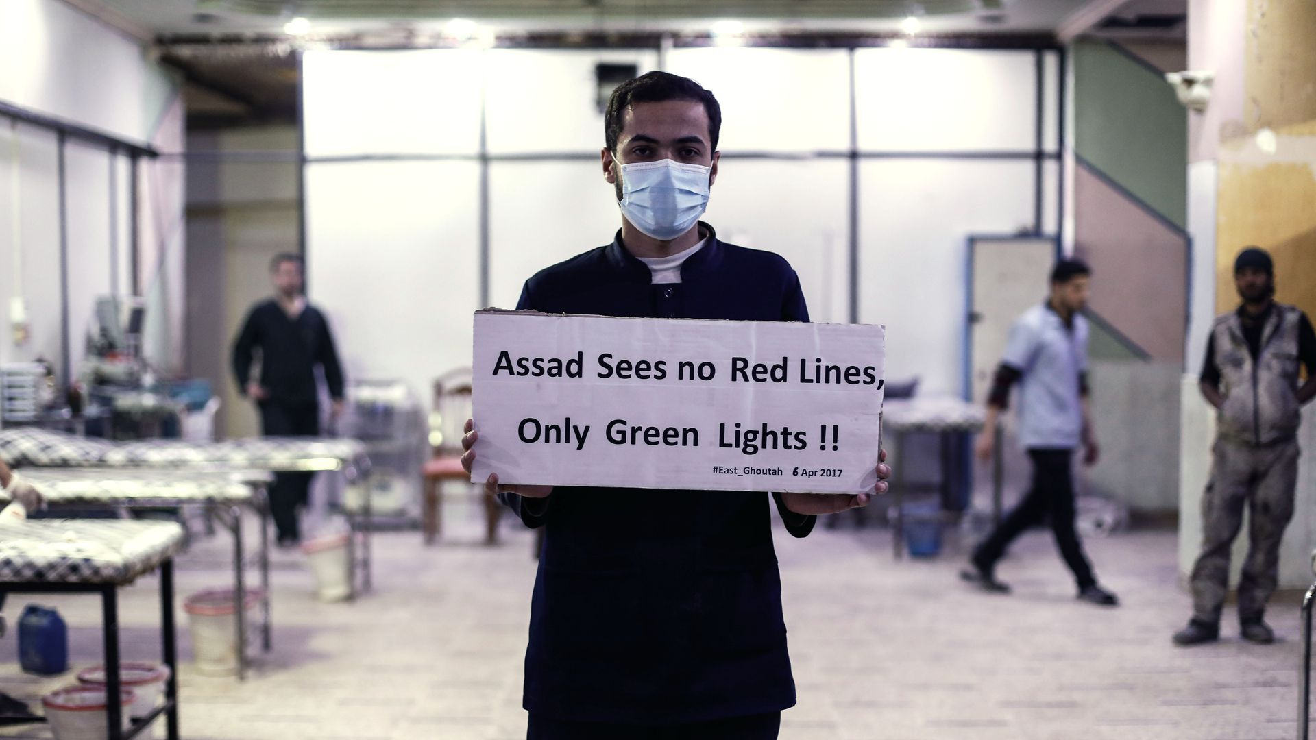 A medical worker at Damascus Countryside Specialised Hospital holds a placard condemning a suspected chemical weapons attack on the Syrian town in April 2017