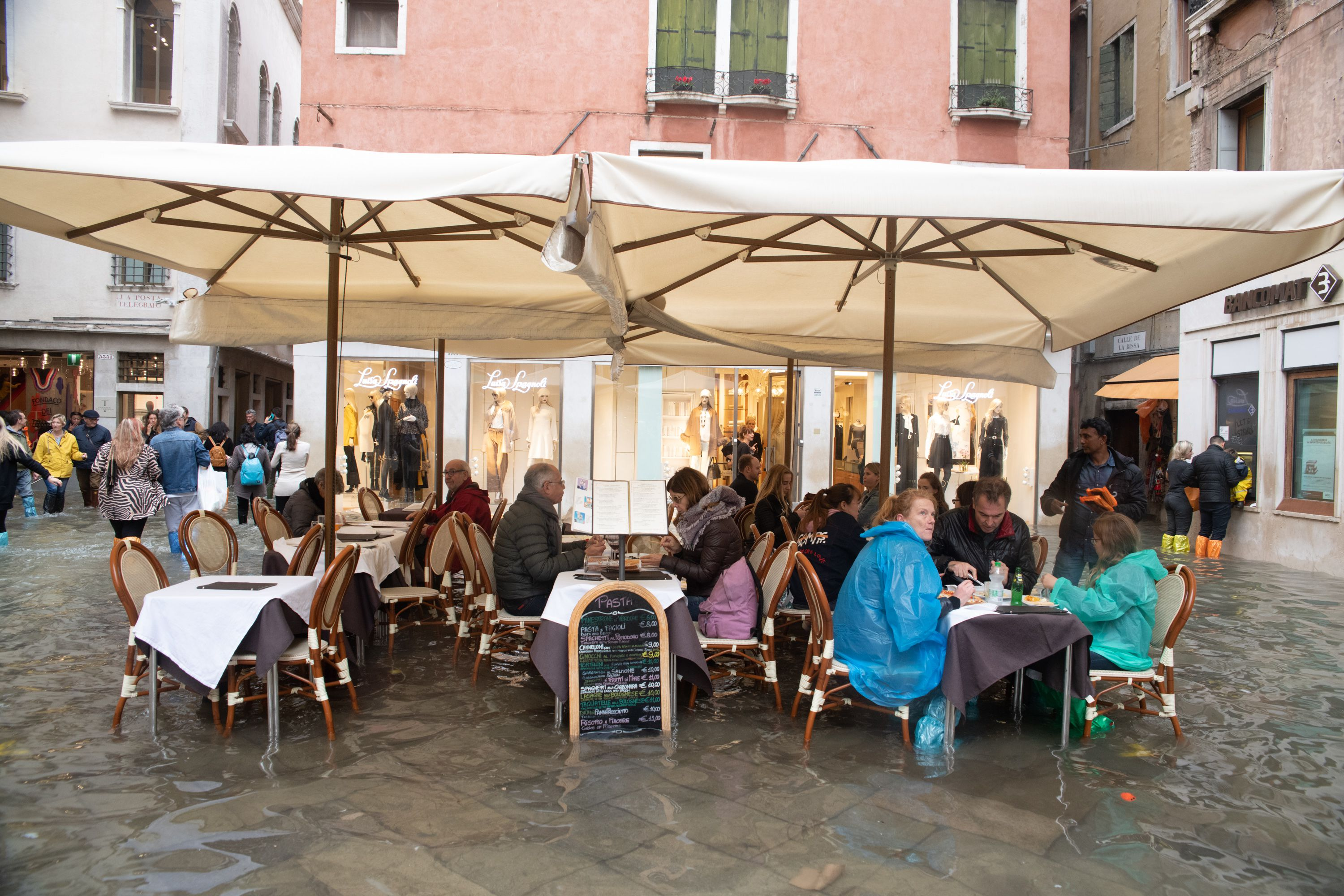 People eating outside in Venice in Ponchos in flooded water.