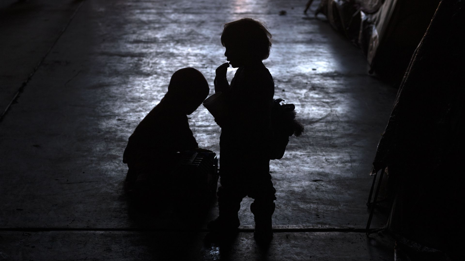 Silhouettes of two young, migrant children at night by the border