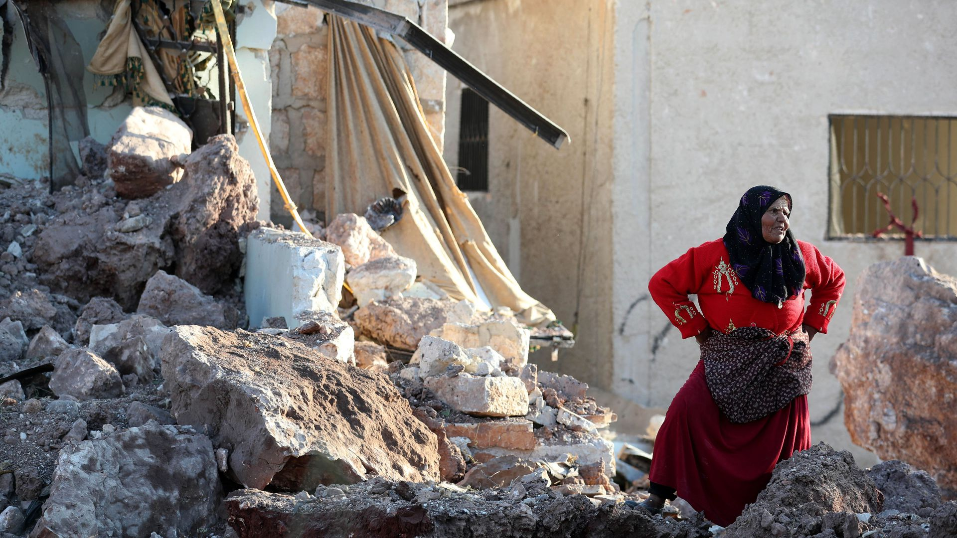 A woman standing in the rubbles following an attack in Idlib, Syria