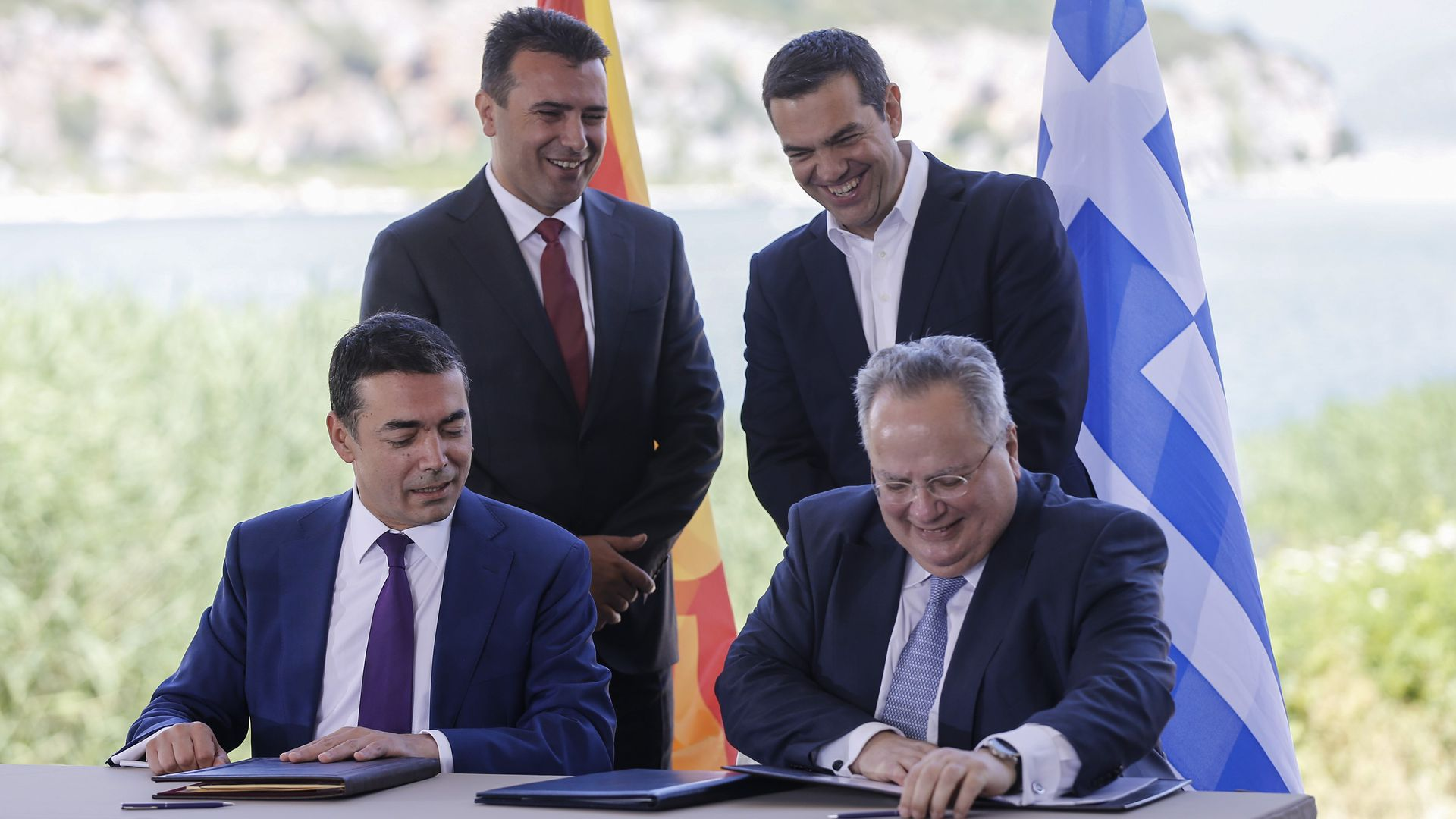 Greek Prime Minister Alexis Tsipras (back R) and Macedonian Prime Minister Zoran Zaev (back L) during the signing ceremony on Sunday.