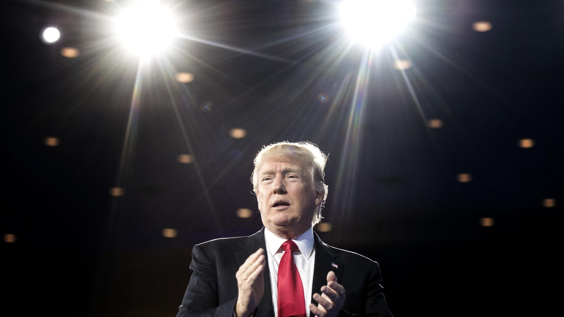 In this image, President Trump stands on stage behind two bright lights.