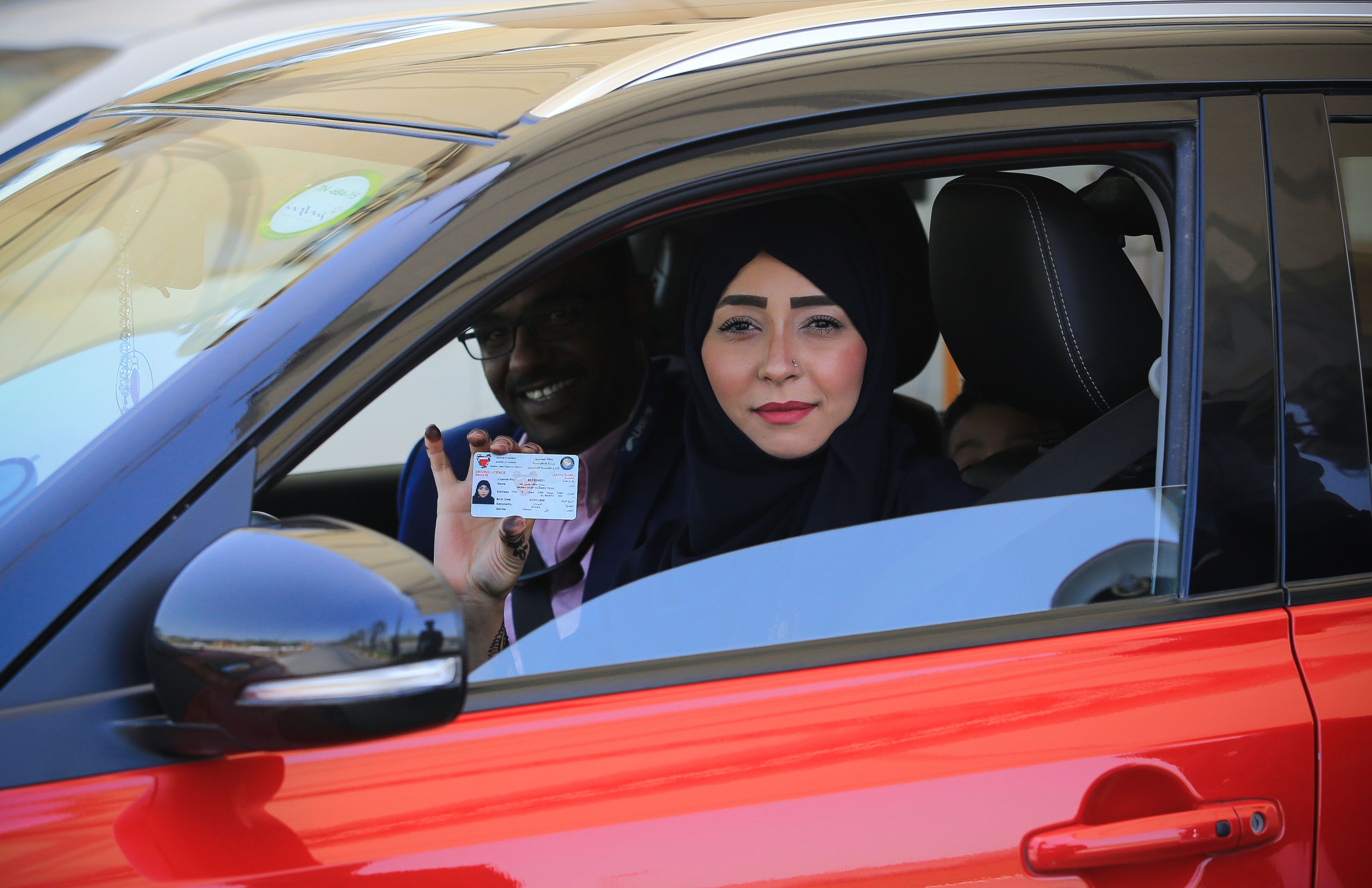 Saudi woman holding up her driver's license