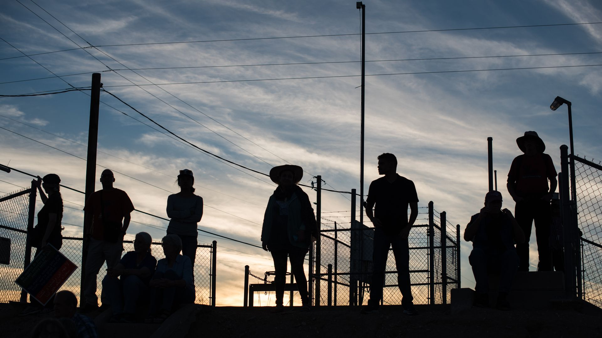 Silouettes of several people standing on a roof with a sunset in the background