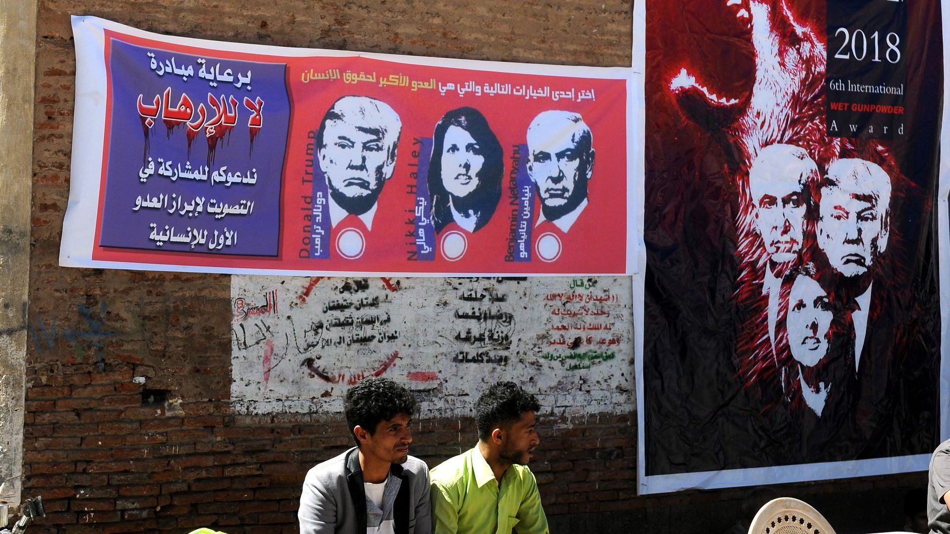 Two Yemeni men under banners showing Donald Trump, Benjamin Netanyahu, and Nikki Haley.