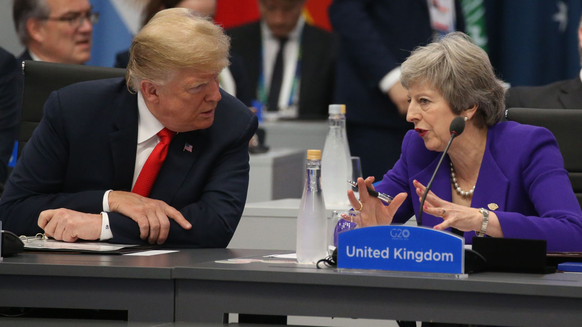 Donald Trump and Theresa May seated next to each other at a conference table