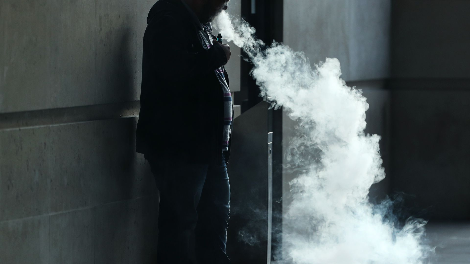 A person blowing smoke from an e-cigarette.