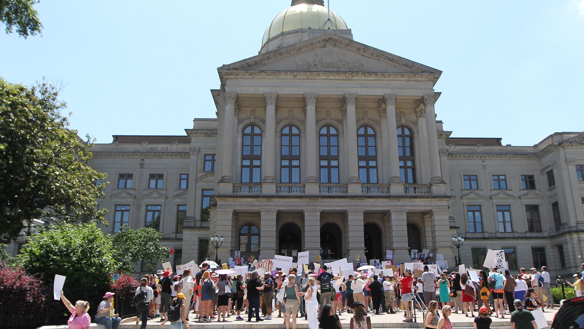 In this image, a crowd of protestors stand outside the the Georgia state capitol building. Many hold signs.