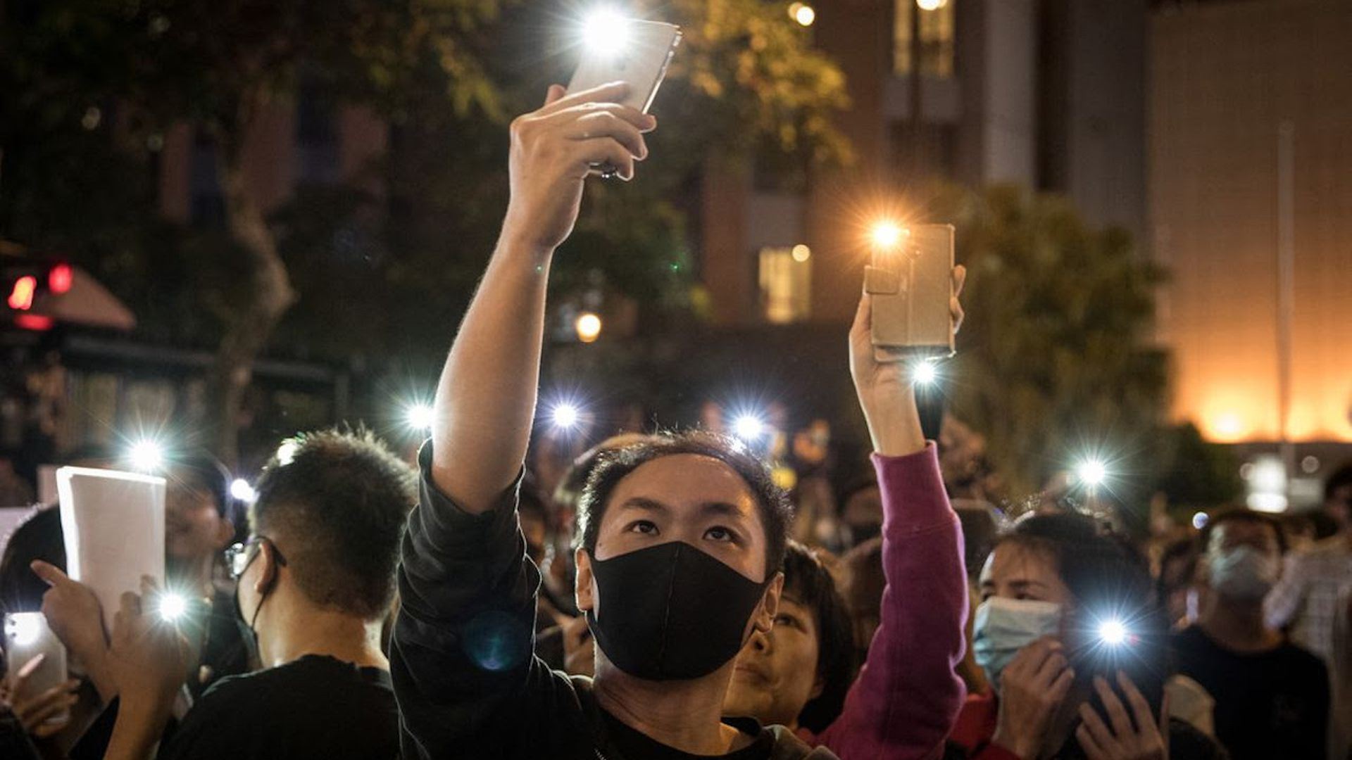 Anti-government protesters shine phone lights at police as they chant slogans in Hong Kong yesterday