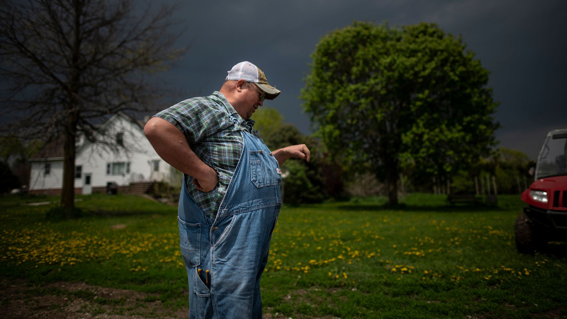 In this image, a farmer in overalls stands in a field with a white house in the background.