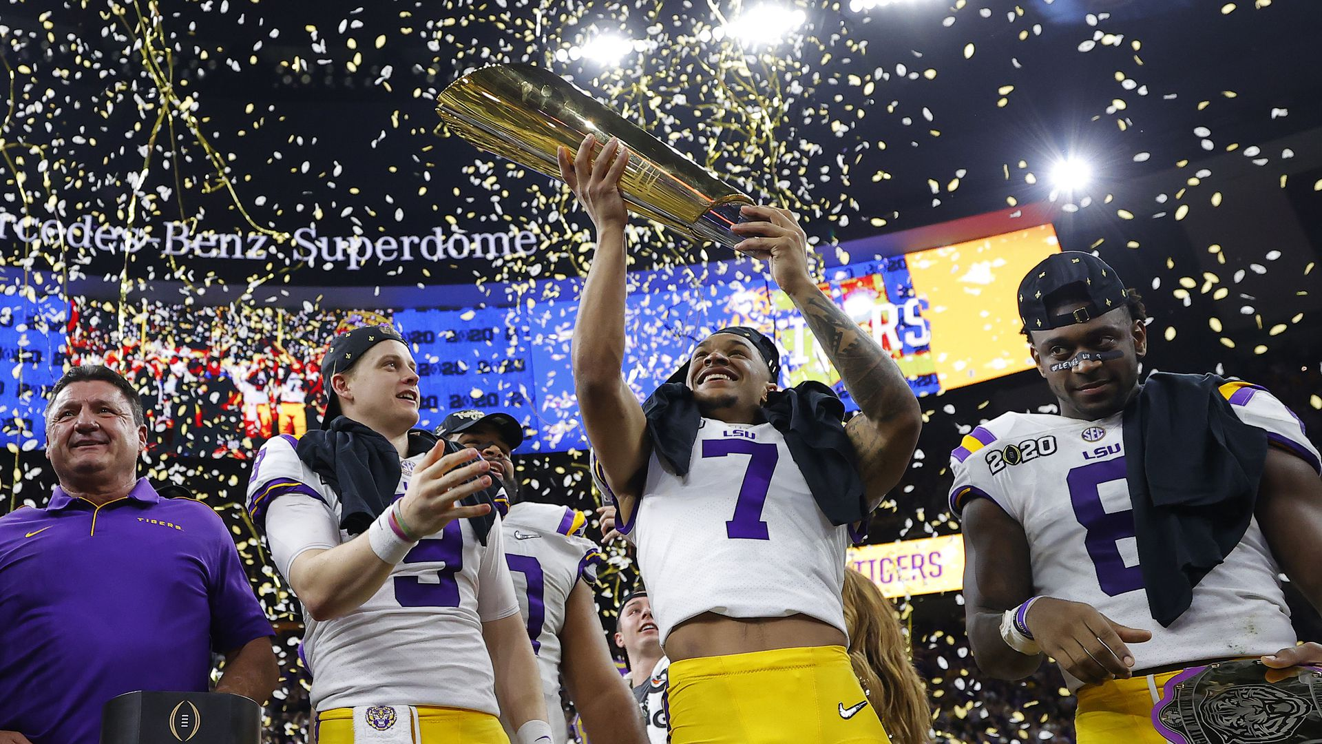 Ed Orgeron of the LSU Tigers, Joe Burrow #9 nd Grant Delpit #7  celebrate with the trophy