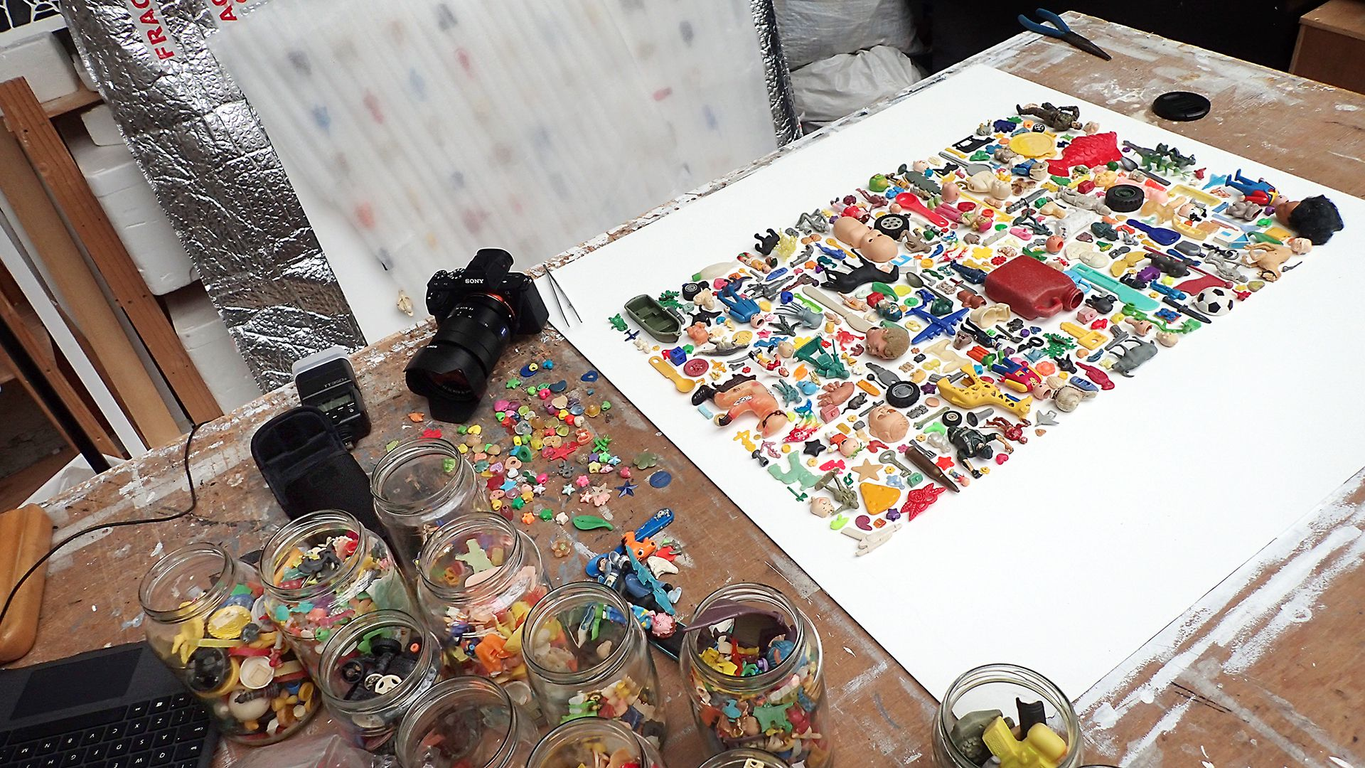 Images of artist's workspace with many glass jars holding assorted small plastic items like toys and beads. Next to it, a canvas with plastic objects arranged in a colorful montage