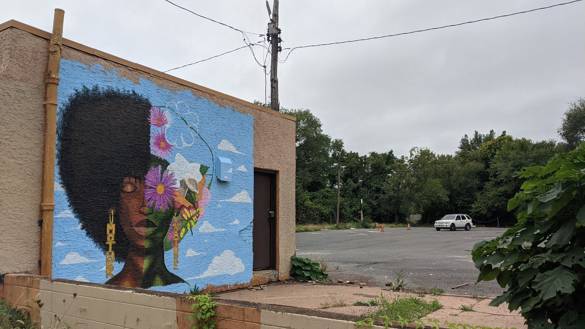 """A mural of an African American woman wearing earrings that read """"Mother"""" and """"Nature"""" is painted on vacant one-story building at N 49th Street and Parkside Avenue in West Philadelphia."""