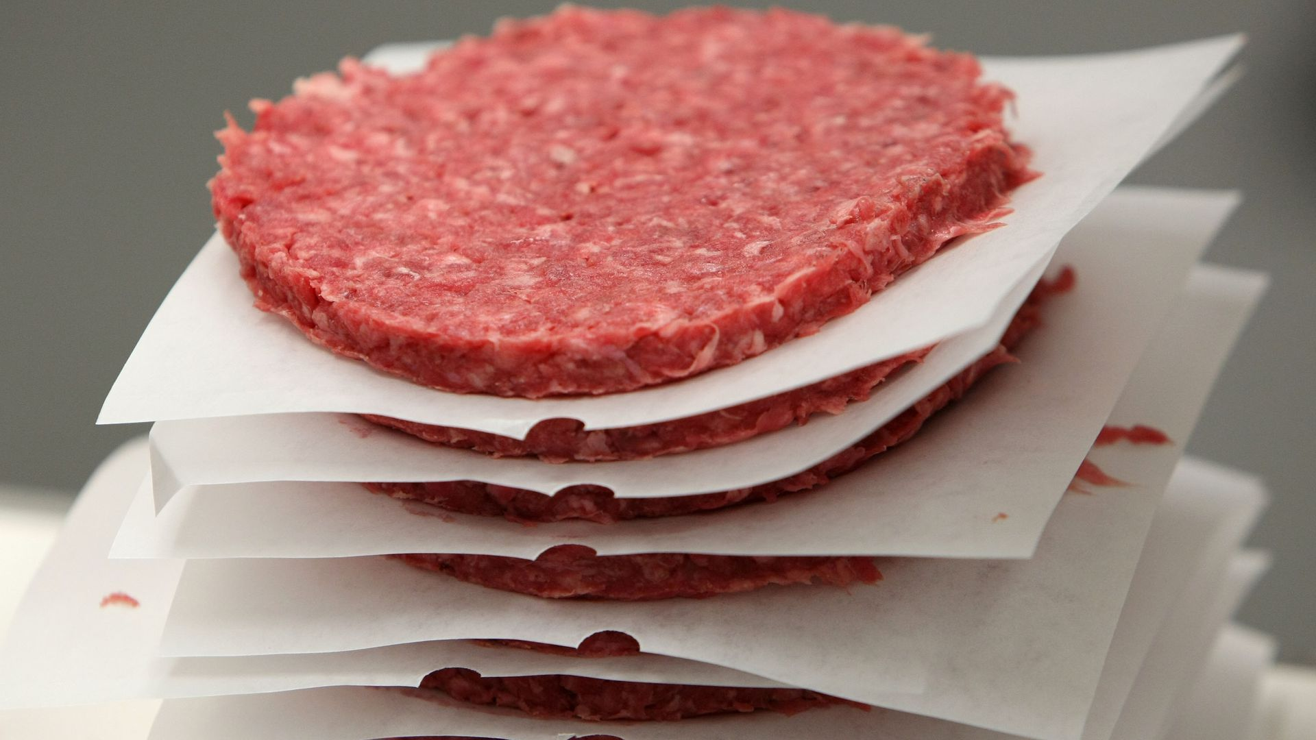 A stack of raw ground beef patties.