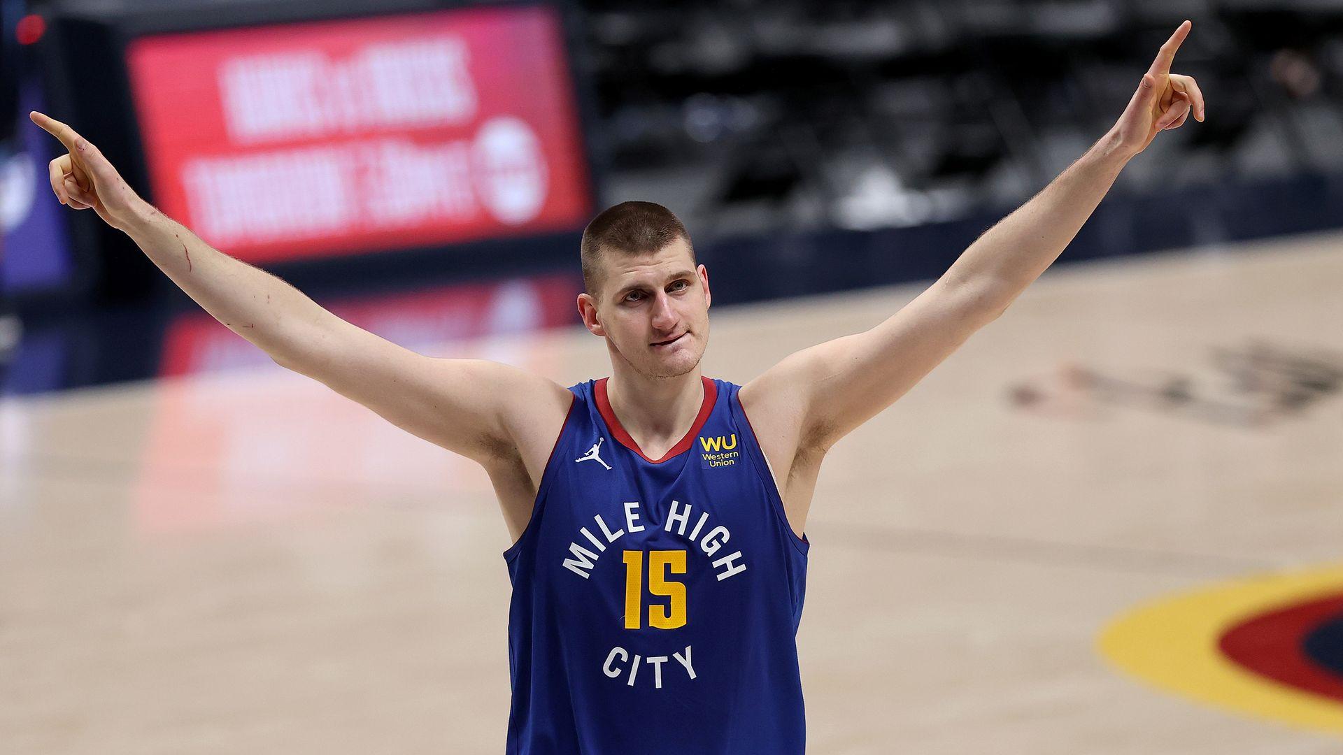 A photo of Nikola Jokic on the basketball court raising his arms in celebration